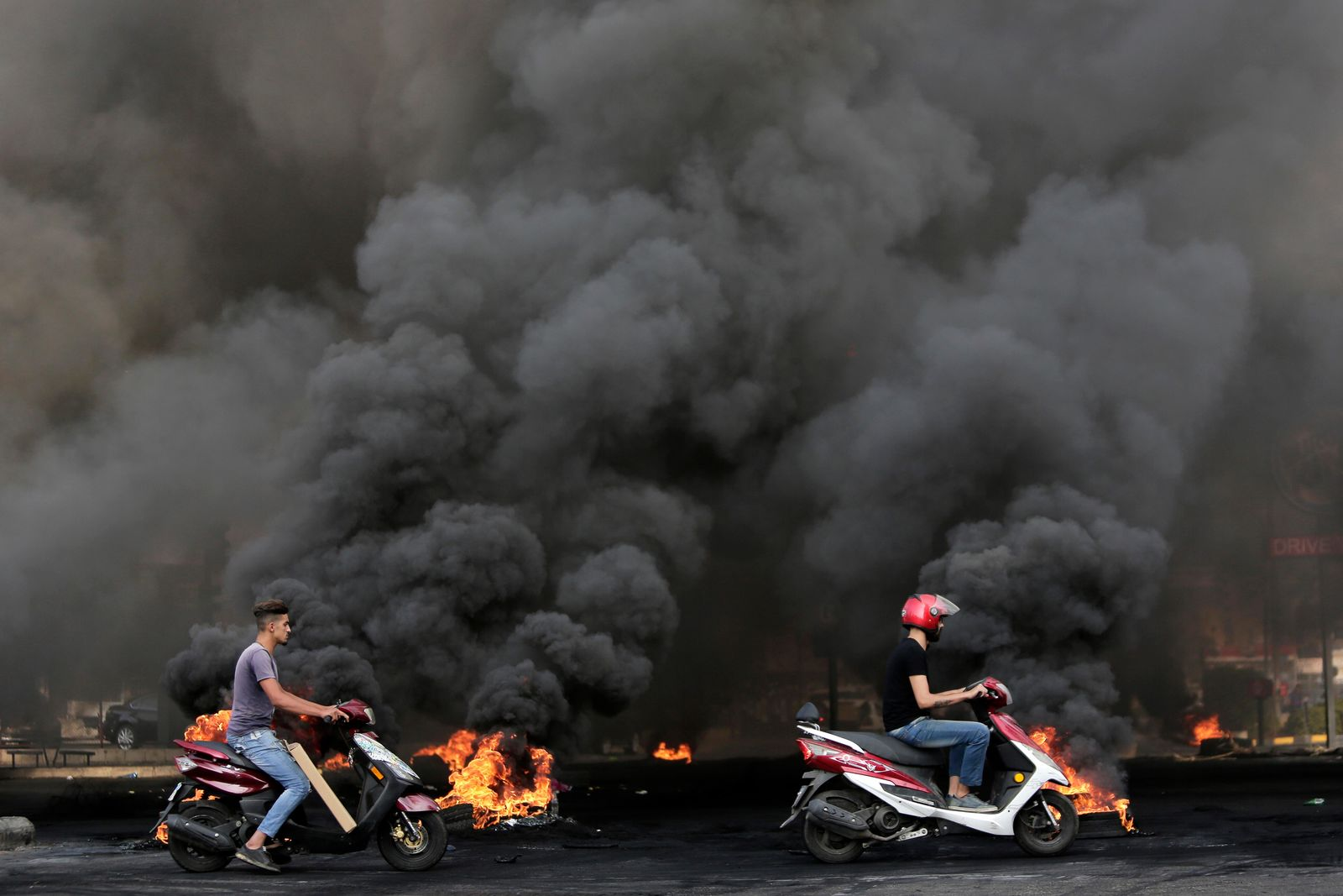 Men on scooters pass tires that were set on fire to block a road during a protest against government's plans to impose new taxes in Beirut, Lebanon, Friday, Oct. 18, 2019. (AP Photo/Hassan Ammar)