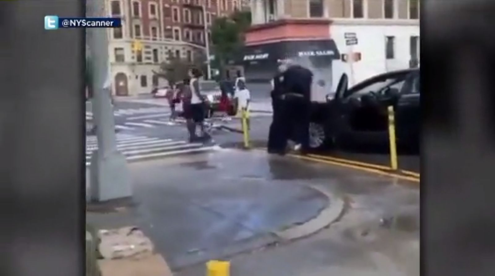 This screenshot of a video uploaded by Twitter used @NYScanner shows police officers in Harlem being doused with water as they make an arrest. (Image: WCBS via CNN Newsource)