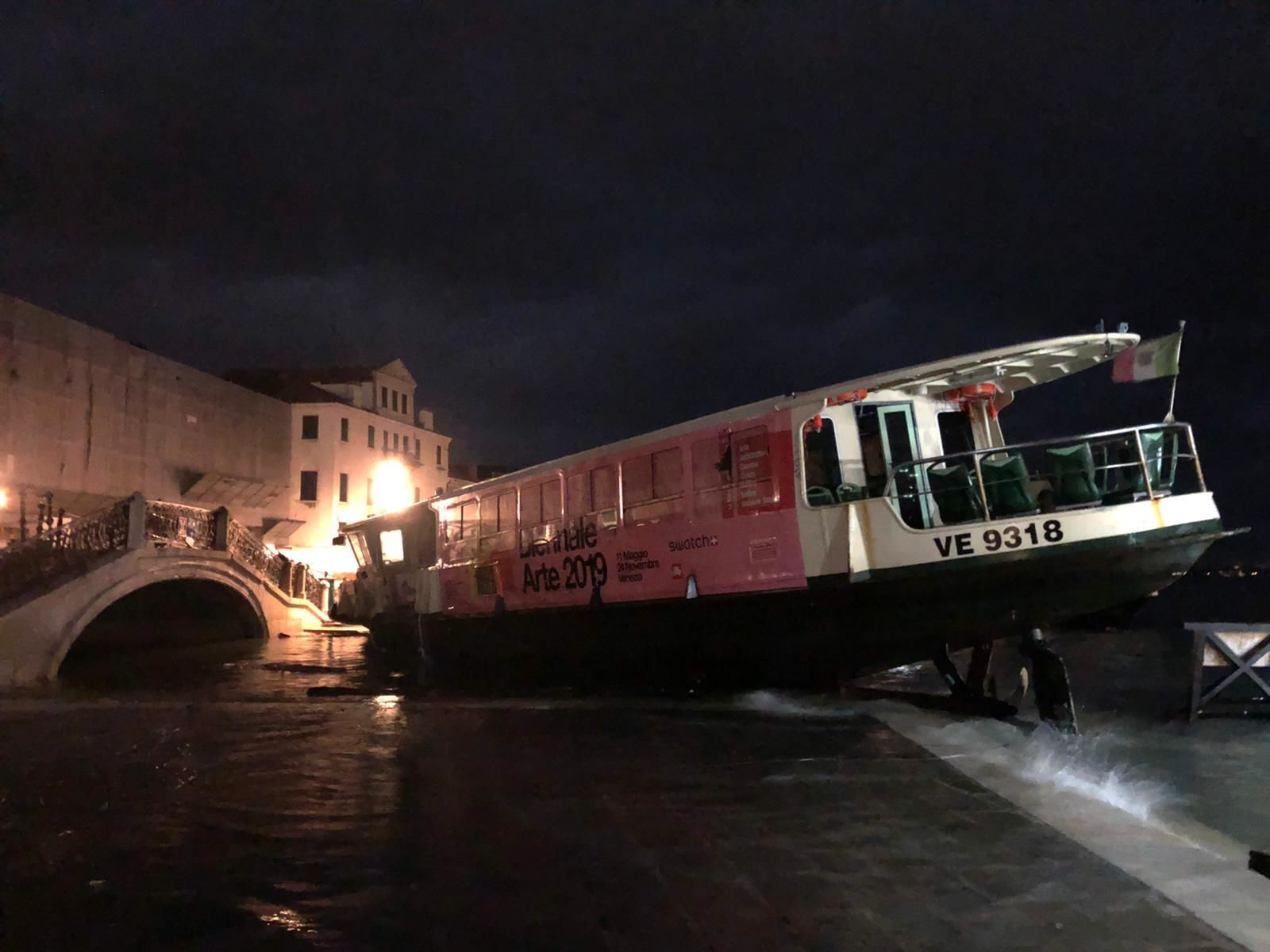 This image made available by the Municipality of Venice shows a ferry stranded on the docks in Venice, Italy, after an exceptional high tide, reaching 1.87 meters above sea level on Tuesday, Nov. 12, 2019.{ } (Venice Municipality via AP)