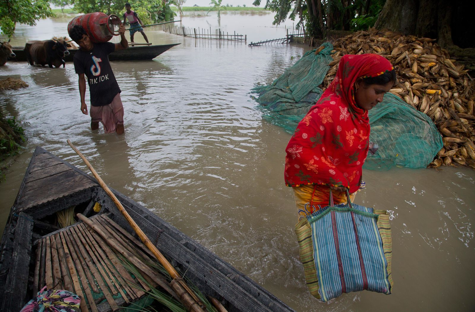 Indian villagers with their belongings wade through flood water in Katahguri village along the river Brahmaputra, east of Gauhati, India, Sunday, July 14, 2019. Officials in northeastern India said more than a dozen people were killed and over a million affected by flooding. Rain-triggered floods, mudslides and lightning have left a trail of destruction in other parts of South Asia. (AP Photo/Anupam Nath)