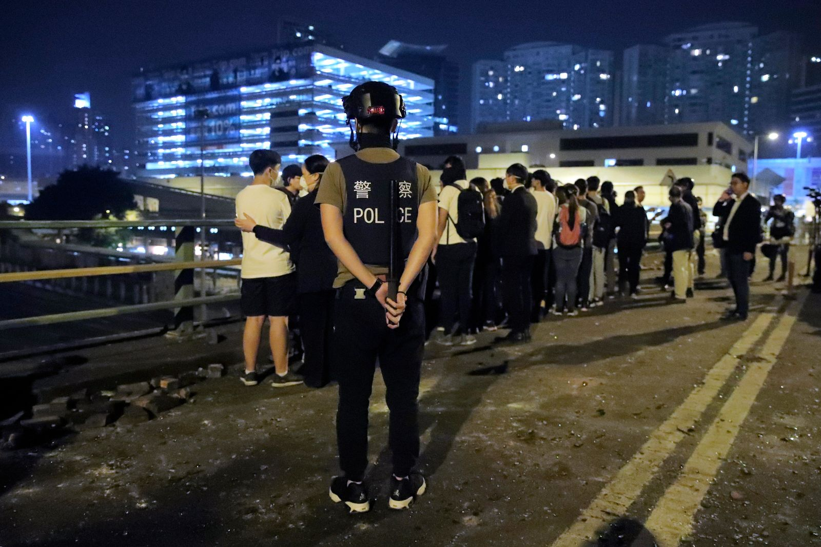 A riot policeman watches over a group of detained people on a bridge in Hong Kong, early Tuesday, Nov. 19, 2019.{ } (AP Photo/Kin Cheung)