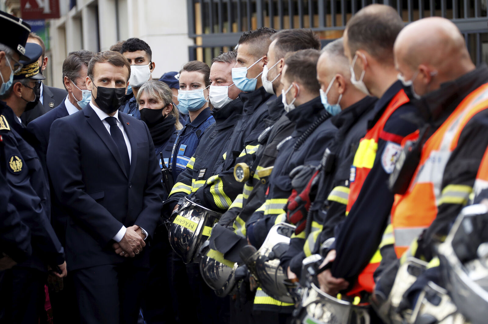 FILE- French President Emmanuel Macron meets rescue workers after a knife attack at Notre Dame church in Nice, southern France, Thursday, Oct. 29, 2020.{ } (Eric Gaillard/Pool via AP)