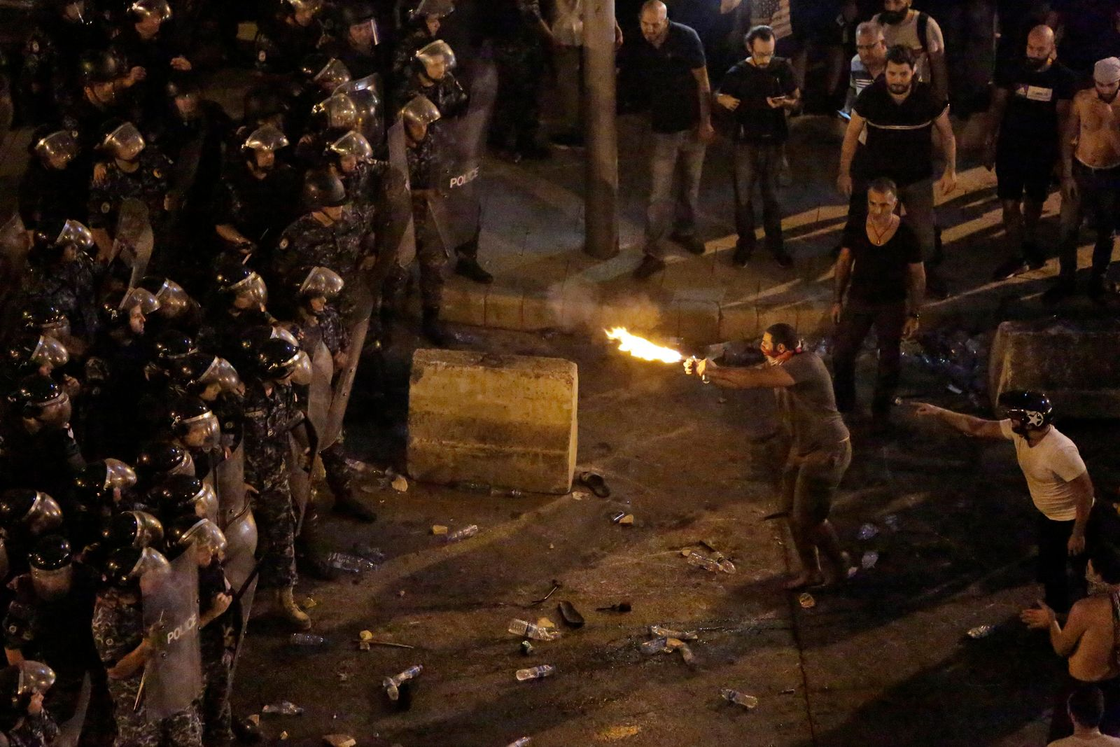 Anti-government protesters clash with riot policemen during a protest against government's plans to impose new taxes in Beirut, Lebanon, Friday, Oct. 18, 2019. (AP Photo/Hassan Ammar)