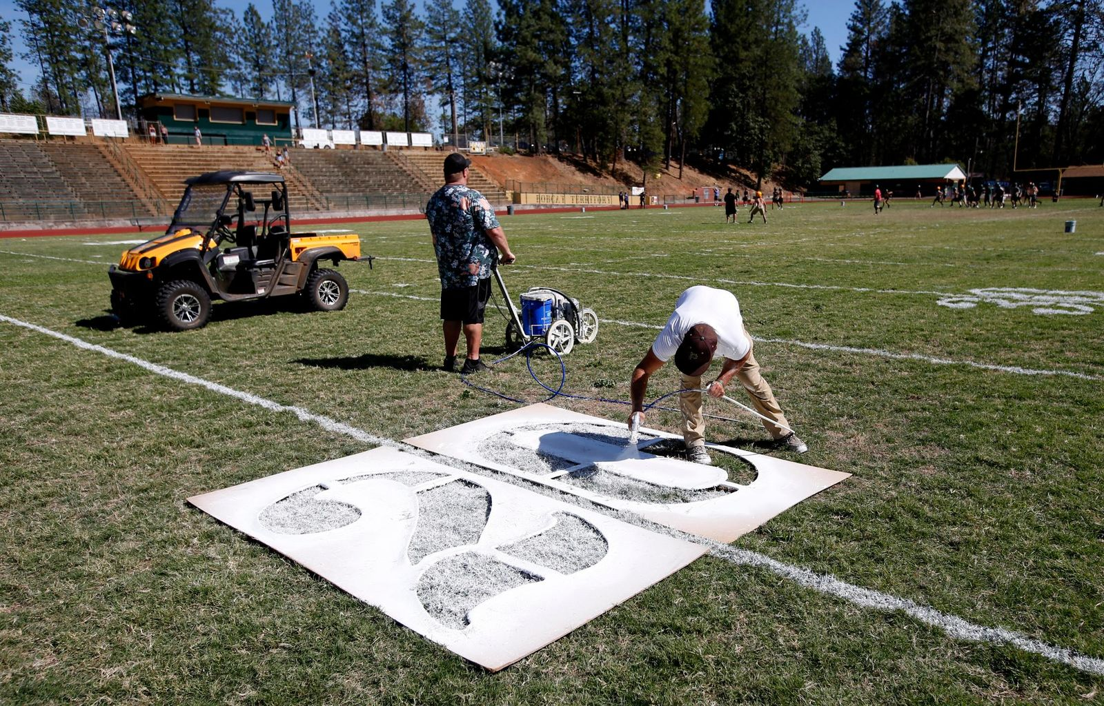 In this Thursday, Aug. 22, 2019, photo, Paul Orlando, right, the defensive coordinator for the Paradise High School football team, paints the numbers on the field in preparation for the teams first game of the season in Paradise, Calif. (AP Photo/Rich Pedroncelli)