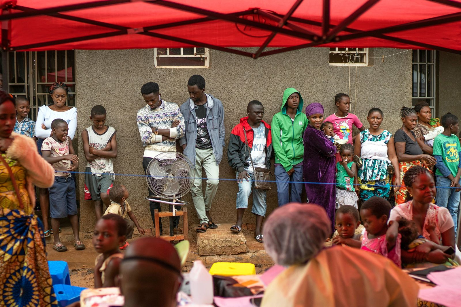 In this photograph taken Saturday July 13, 2019, residents wait in line to receive the Ebola vaccine in Beni, Congo DRC. The head of the World Health Organization is convening a meeting of experts Wednesday July 17, 2019, to decide whether the Ebola outbreak should be declared an international emergency after spreading to eastern Congo's biggest city, Goma, this week. More than 1,600 people in eastern Congo have died as the virus has spread in areas too dangerous for health teams to access. (AP Photo/Jerome Delay)