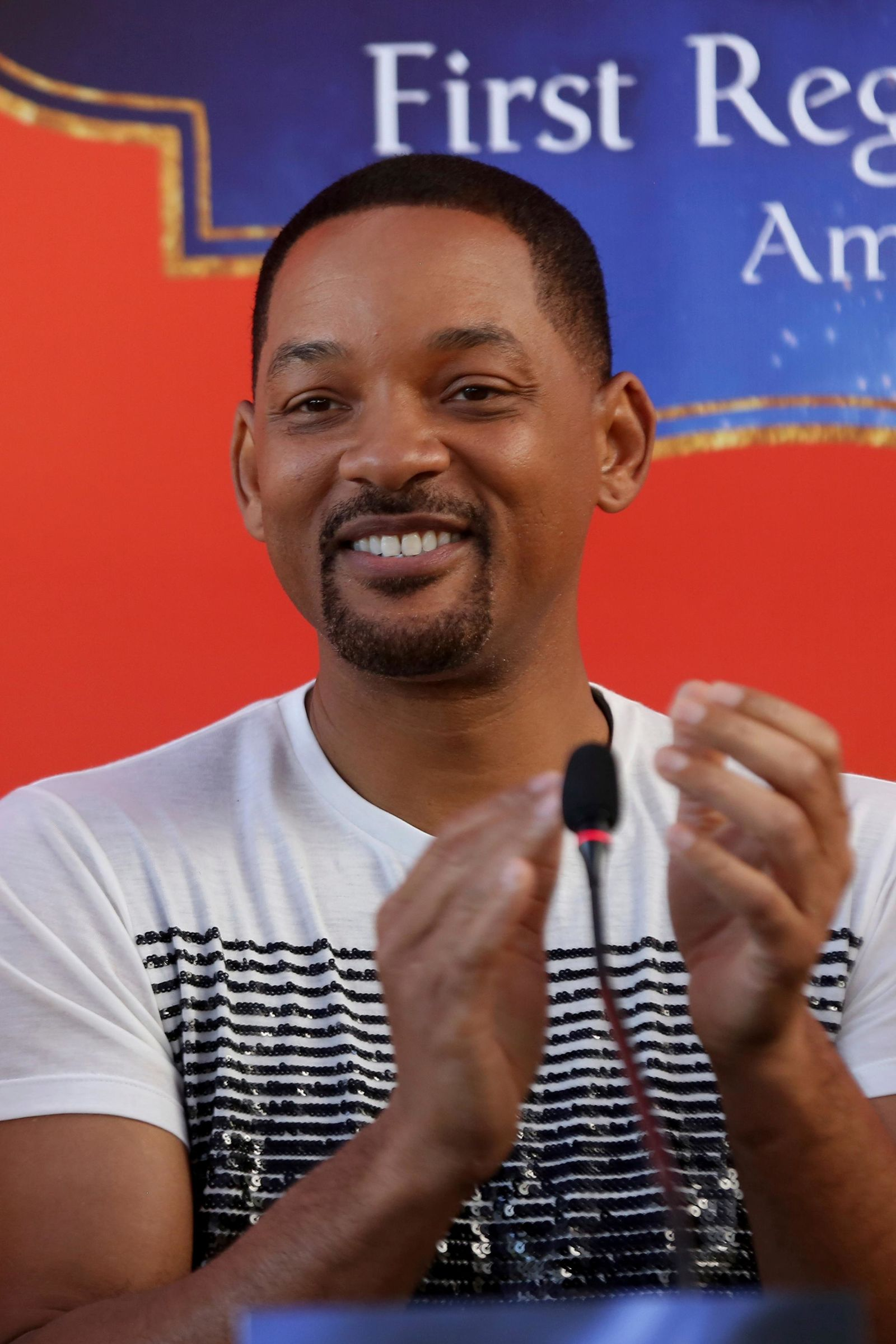 "U.S. actor Will Smith applauds during a news conference with the director Guy Ritchie and stars Mena Massoud and Naomi Scott, ahead of the regional launching of Disney's live-action ""Aladdin,"" in the Jordanian capital Amman. (AP Photo/Raad Adayleh)"