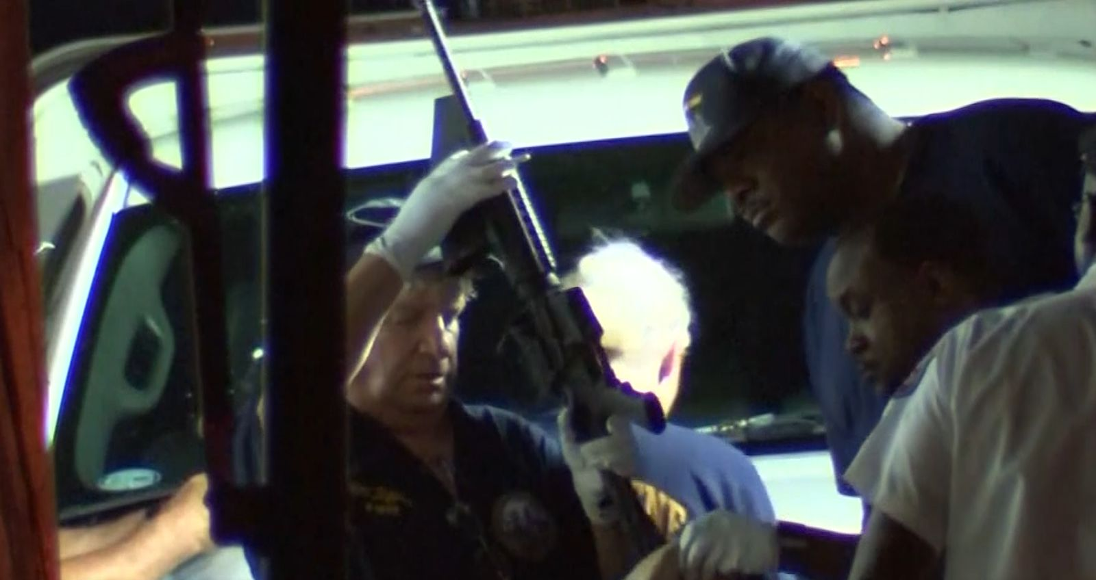 Officers remove an AR-15 from the home where a gunman opened fire on Philadelphia police. (KYW/CNN Newsource)