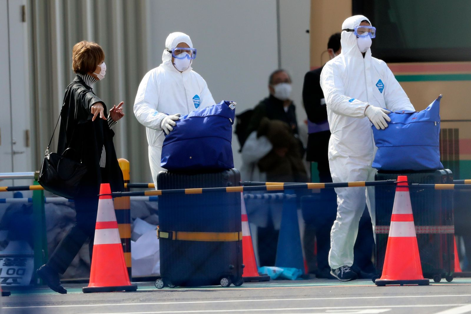 Officials in protective suits help a passenger disembarked from the quarantined Diamond Princess cruise ship anchored at a port in Yokohama, near Tokyo, Thursday, Feb. 20, 2020.{ } (AP Photo/Eugene Hoshiko)