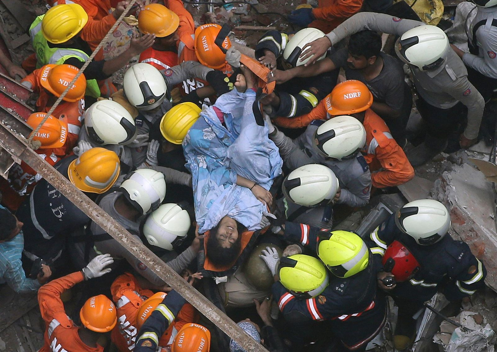 Rescuers carry out a survivor from the site of a building that collapsed in Mumbai, India, Tuesday, July 16, 2019.{ } (AP Photo/Rajanish Kakade)