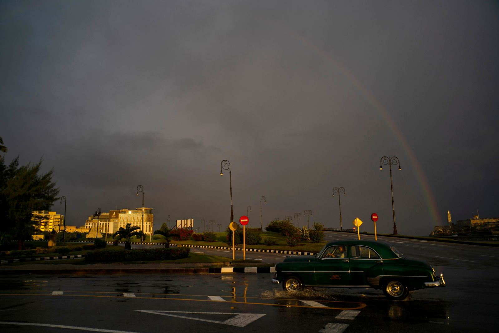 In this Nov. 10, 2019 photo, under a rainbow, a man drives a classic American car past the newly opened Hotel Paseo del Prado in Havana, Cuba. The city will celebrate its 500th anniversary on Nov. 16. (AP Photo/Ramon Espinosa)