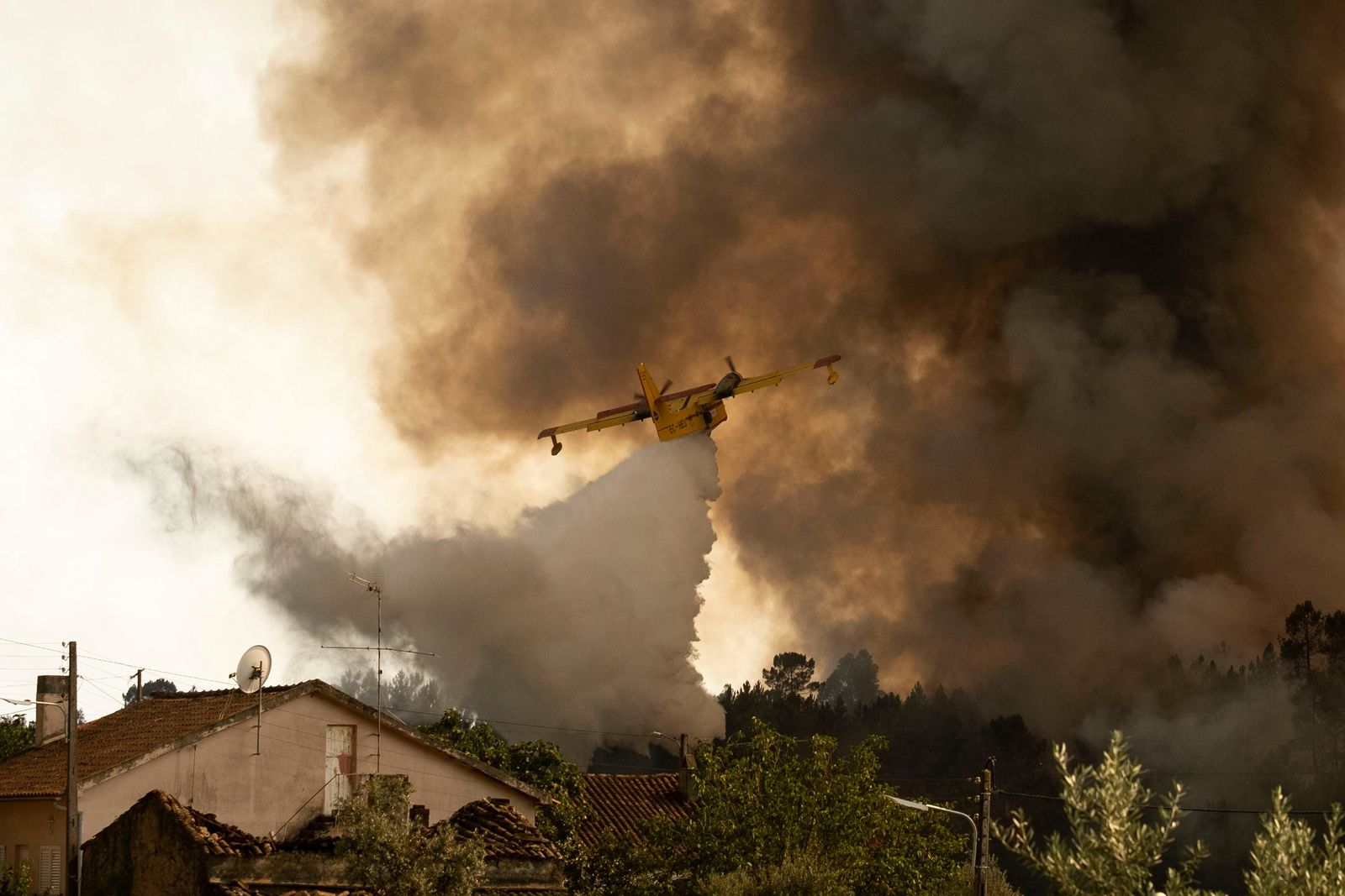 An airplane operates over a fire at the village of Chaveira, near Macao, in central Portugal on Monday, July 22, 2019 (AP Photo/Sergio Azenha)