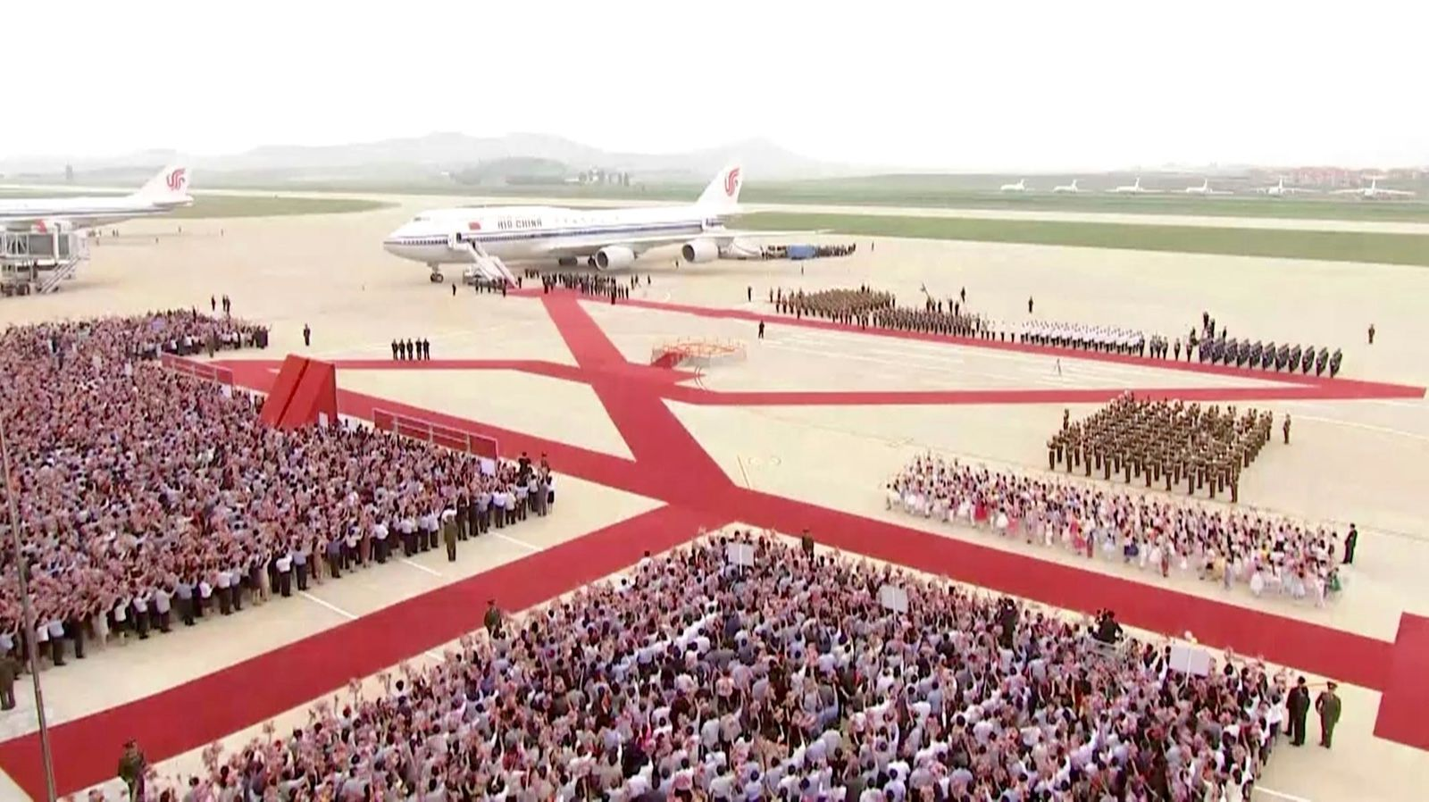In this image made from video, North Korean people and a guard of honor welcome a plane with Chinese President Xi Jinping onboard, on the arrival at an airport in Pyongyang, Thursday, June 20, 2019.{ } (CCTV via AP)