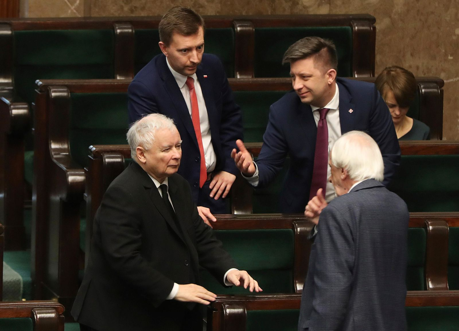 Jaroslaw Kaczynski,left, leader of the conservative ruling party Law and Justice, speaks with other members of his party in parliament in Warsaw, Poland, Friday April 3, 2020. .(AP Photo/Czarek Sokolowski)
