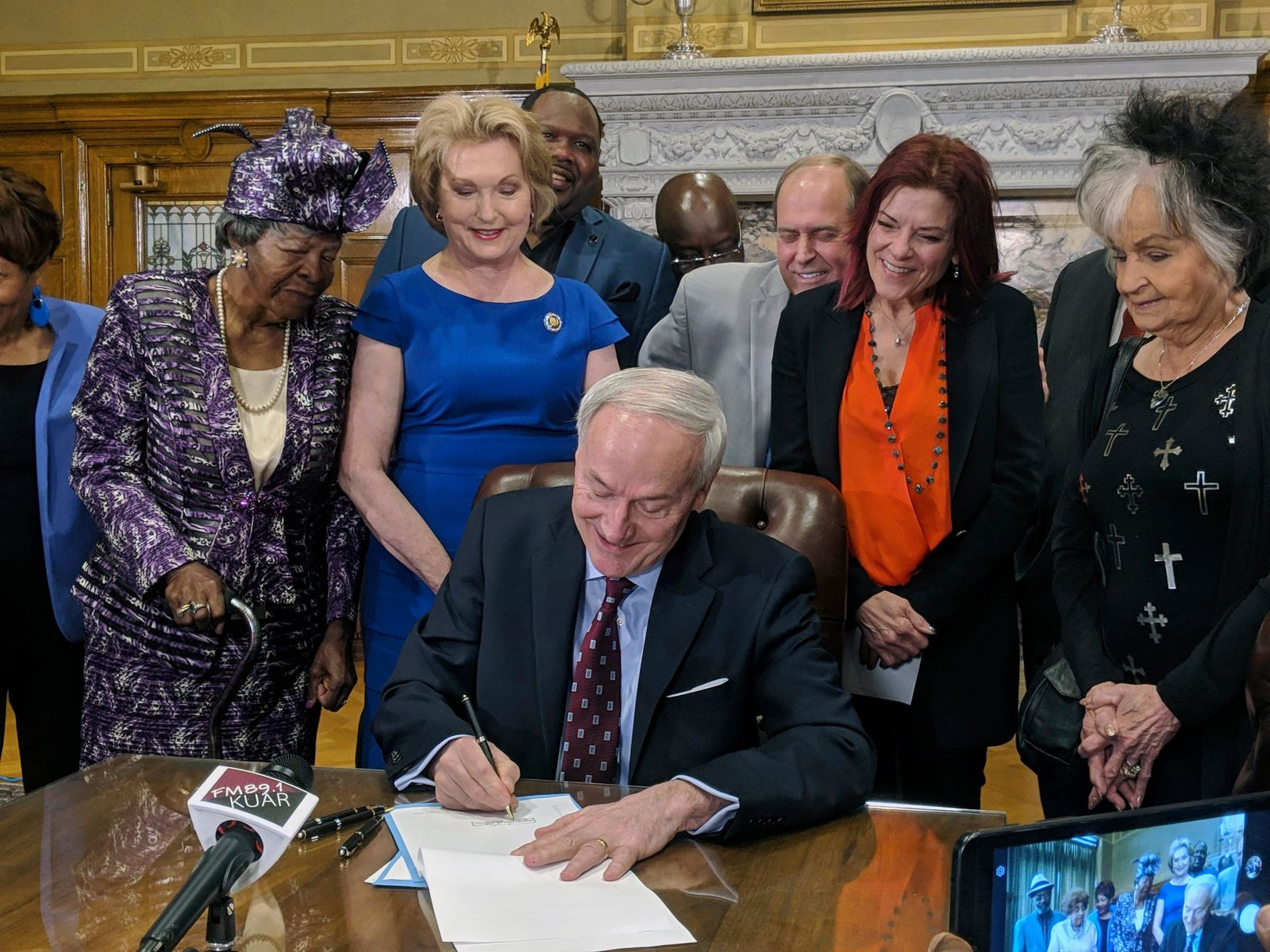 Arkansas Gov. Asa Hutchinson signs a bill into law that replaces two statues in a U.S. Capitol display with statues of civil rights leader Daisy Bates and country musician Johnny Cash, Thursday, April 11, 2019, in Little Rock, Ark. The governor was joined by friends and family of Bates and Cash. They will replace statues of attorney Uriah Milton Rose and former Gov. and Sen. James Paul Clarke. (AP Photo/Hannah Grabenstein)