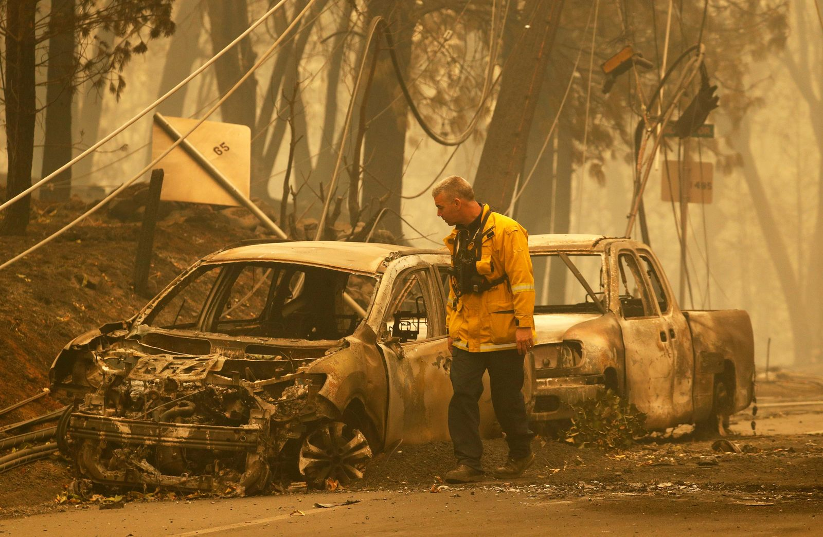 A Sonoma Valley firefighter inspects burned out cars to make sure they are clear of human remains, Friday, Nov. 9, 2018, in Paradise, Calif. (AP Photo/John Locher)
