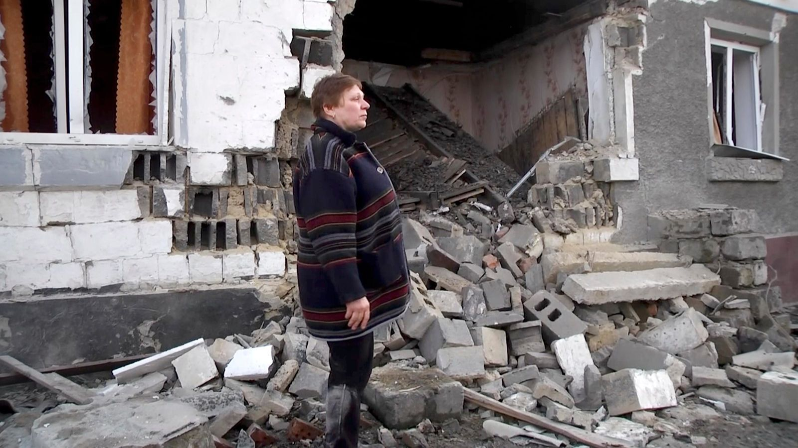 In this video grab provided by the RU-RTR Russian television, a woman stands next to her home, that was distroyed during cross fire between Russia-backed separatists and Ukrainian forces, in Zaitseve, Donetsk region, eastern Ukraine, Tuesday, Feb. 18, 2020.{ } { }(RU-RTR Russian Television via AP)