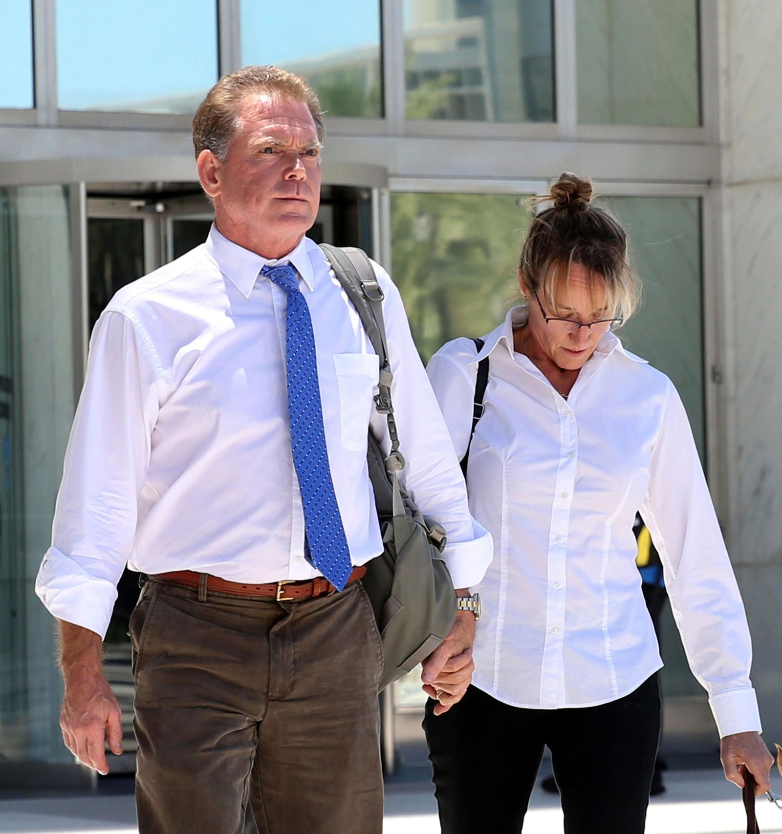 FILE - In this July 10, 2019, file photo, Douglas Haig, left, the Arizona man who sold ammunition to the Route 91 Harvest festival gunman, and his wife, Dori, leave the Lloyd George Federal Courthouse in Las Vegas. Haig is due to plead guilty to illegally manufacturing tracer and armor-piercing bullets found in a high-rise hotel suite from which a gunman carried out the Las Vegas Strip massacre two years earlier. (Bizuayehu Tesfaye/Las Vegas Review-Journal via AP, File)