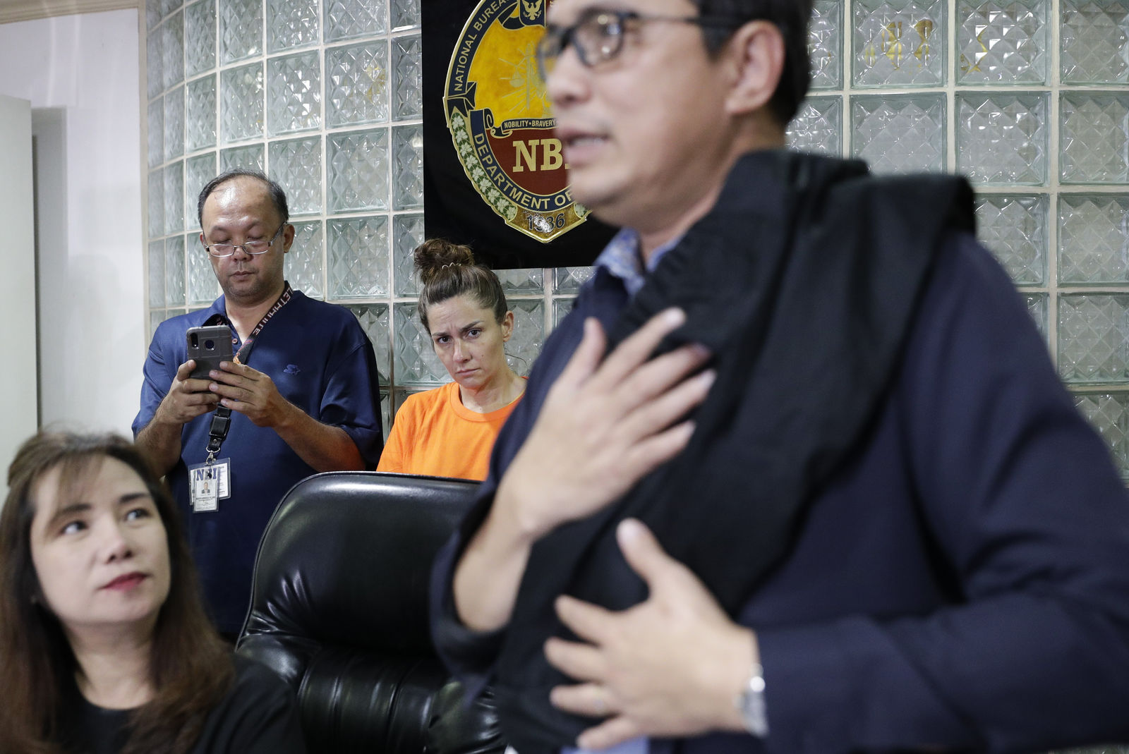 American Jennifer Erin Talbot, center rear, from Ohio looks as National Bureau of Investigation - International Airport Investigation Division chief Atty. Manny Dimaano shows a bag which Talbot allegedly used to carry a baby during a press conference in Manila, Philippines on Thursday, Sept. 5, 2019. (AP Photo/Aaron Favila)