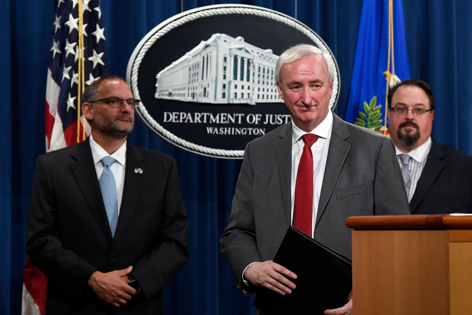 Deputy Attorney General Jeffrey Rosen, center, flanked by Hugh Hurwitz, left, the acting director of the Bureau of Prisons, and David Muhlhausen, director of the National Institute of Justice, listen as a reporter asks a question during a news conference at the Justice Department in Washington, Friday, July 19, 2019, on developments in the implementation of the First Step Act.{ } (AP Photo/Susan Walsh)