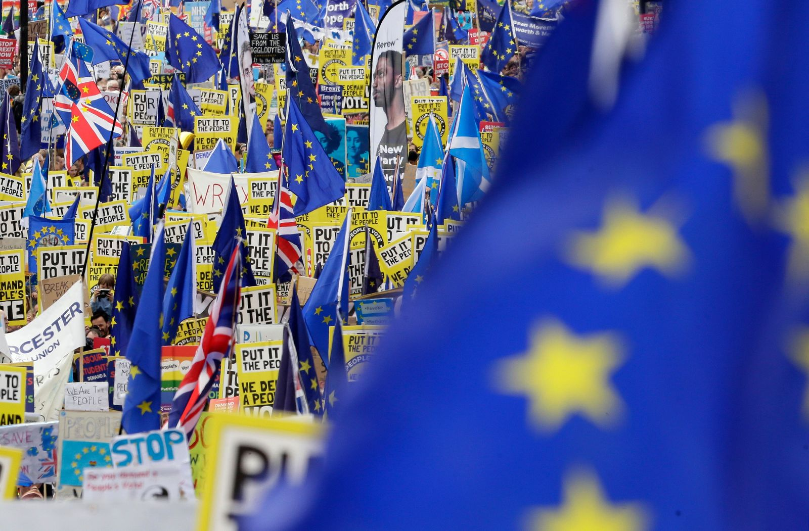 Demonstrators carry posters and flags during a Peoples Vote anti-Brexit march in London, Saturday, March 23, 2019.{ } (AP Photo/Tim Ireland)