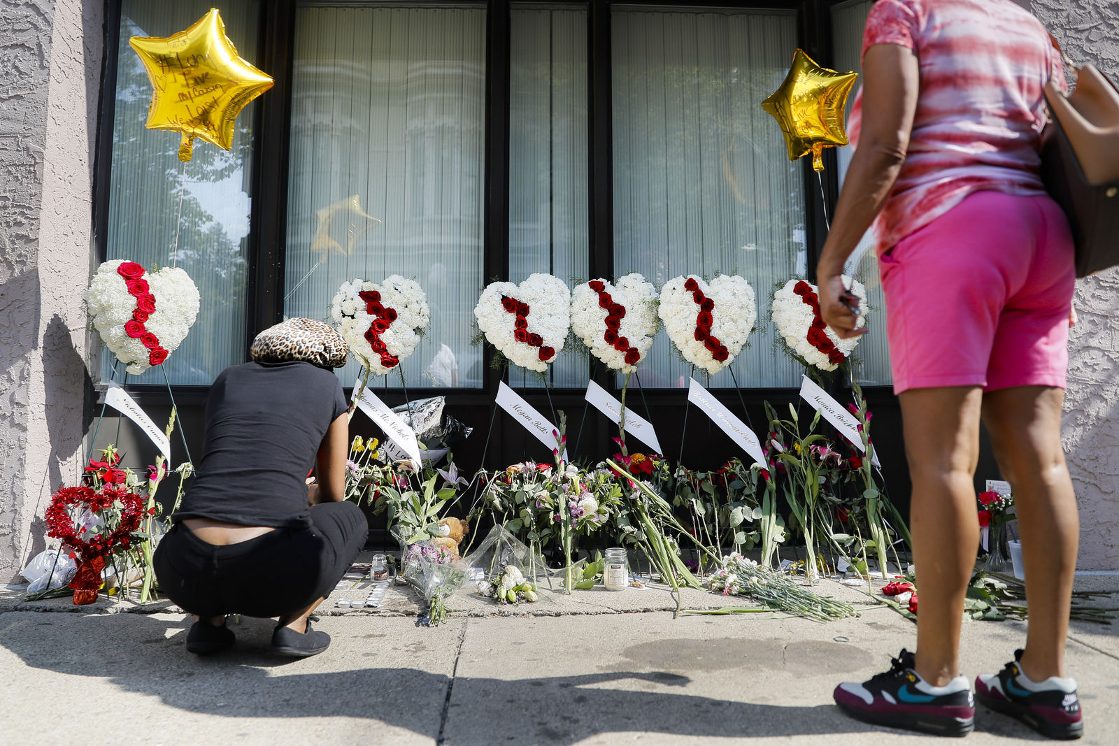 Mourners pause at a makeshift memorial Tuesday, Aug. 6, 2019, for the slain and injured in the Oregon District after a mass shooting that occurred early Sunday morning, in Dayton. (AP Photo/John Minchillo)