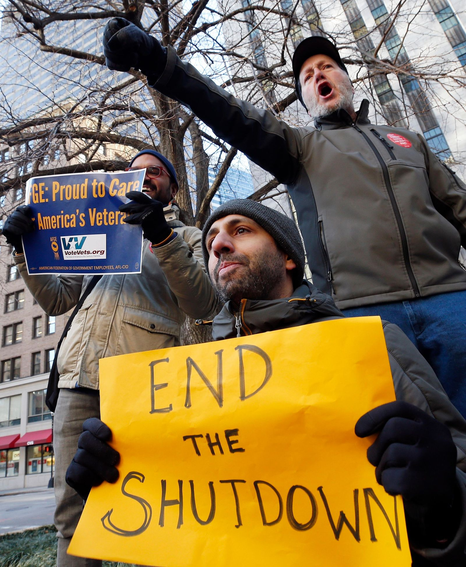 Government workers and their supporters hold signs during a protest in Boston, Friday, Jan.11, 2019.{ } (AP Photo/Michael Dwyer)