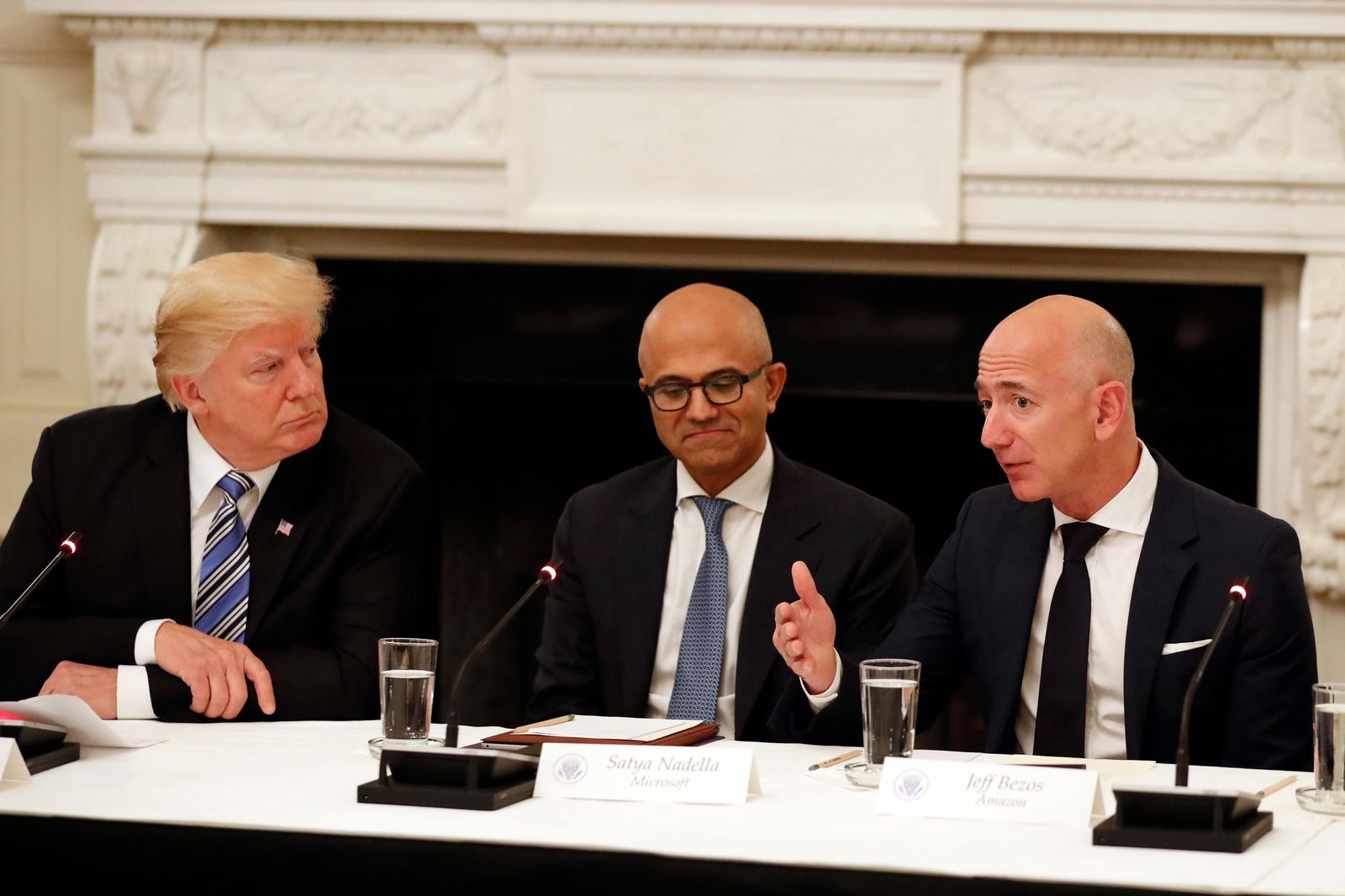 FILE - In this June 19, 2017, file photo President Donald Trump, left, and Satya Nadella, Chief Executive Officer of Microsoft, center, listen as Jeff Bezos, Chief Executive Officer of Amazon, speaks during an American Technology Council roundtable in the State Dinning Room of the White House in Washington.{ } (AP Photo/Alex Brandon, File)