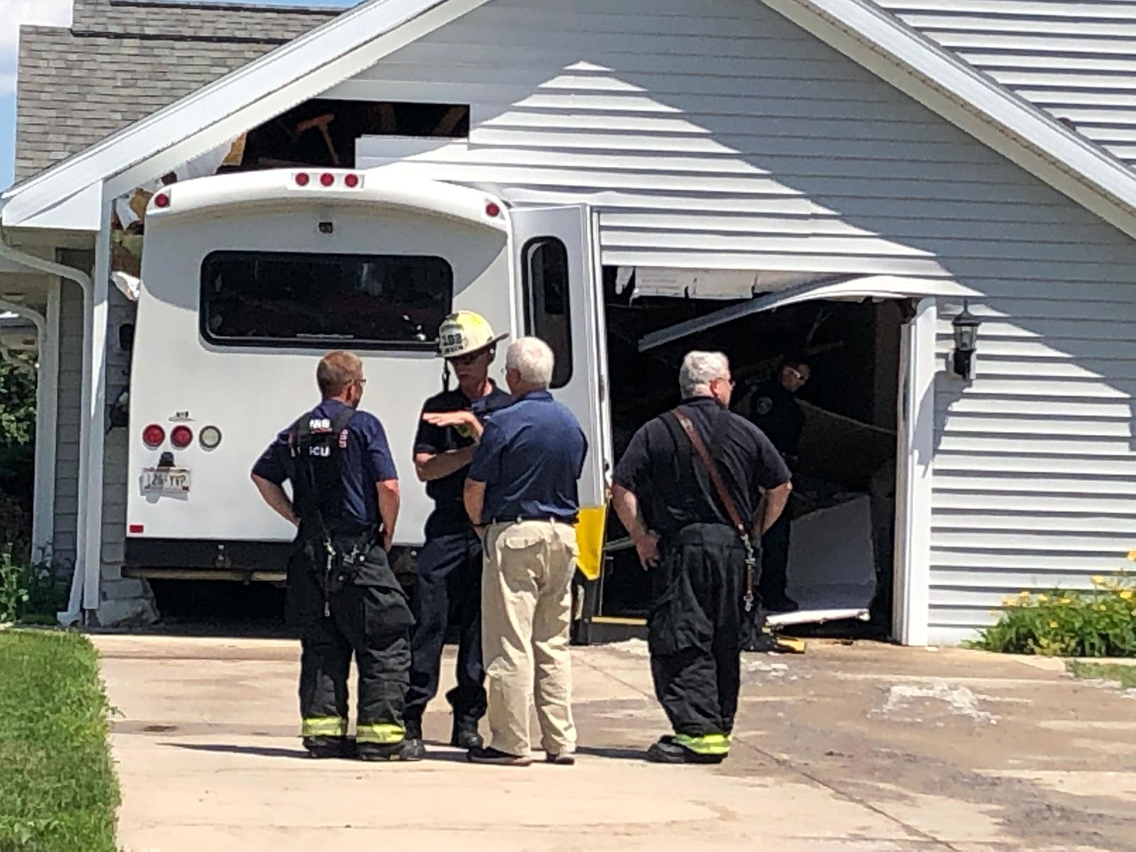 Firefighters investigate as a van is wedged into the garage of a building in De Pere July 10, 2019. (WLUK/Jessie Basinski)