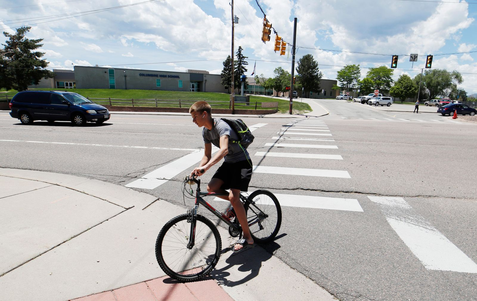 A bicyclist rides away from Columbine High School, Thursday, June 13, 2019, in Littleton, Colo. The school district is considering the demolition of Columbine, the scene of a mass assault more than 20 years ago, and rebuilding the current school. (AP Photo/David Zalubowski)