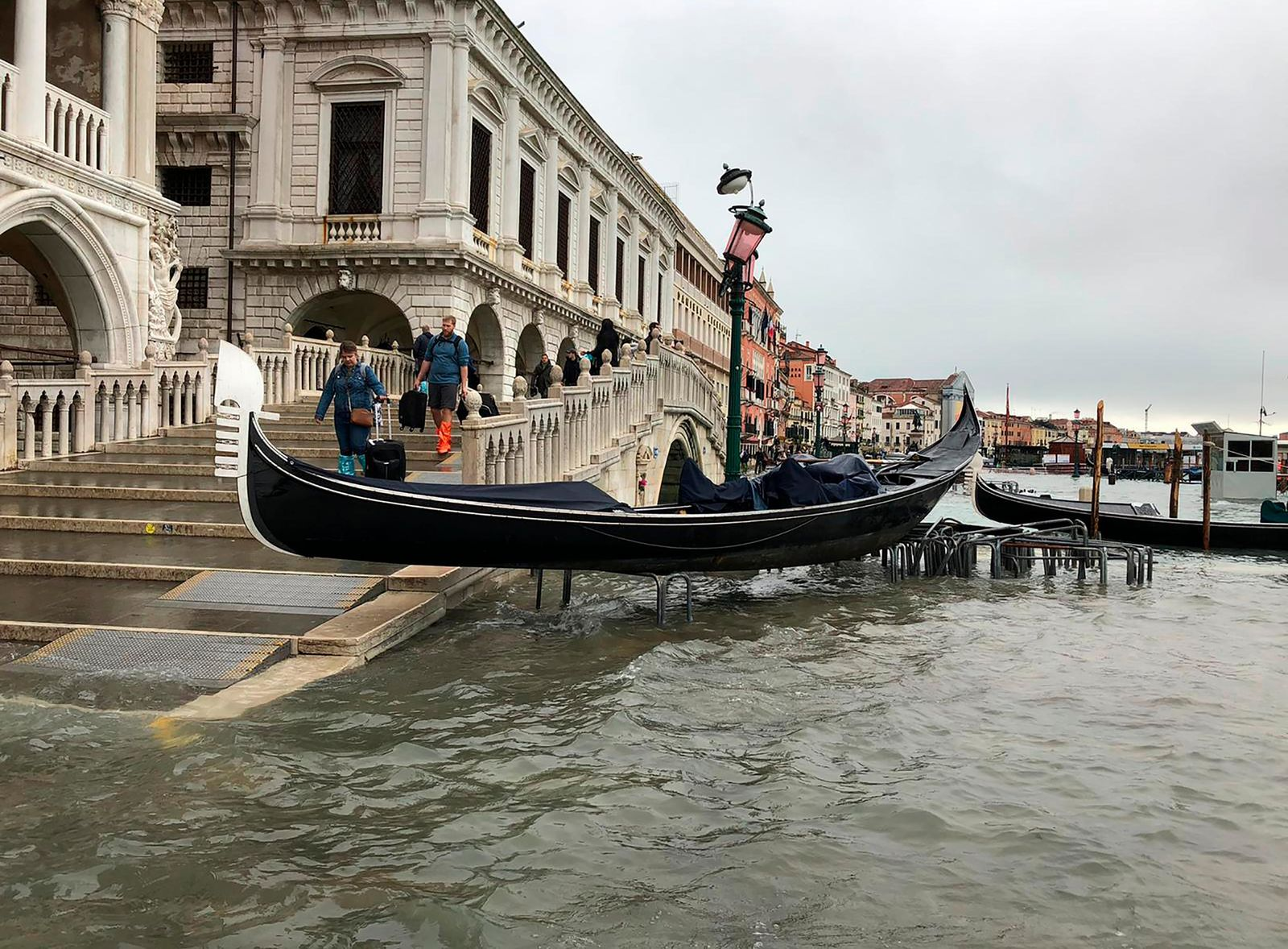 A gondola boat is stranded atop a bike rack after high tide in Venice, Italy, Wednesday, Nov. 13, 2019.{ } (Alessandra Rallo via AP)