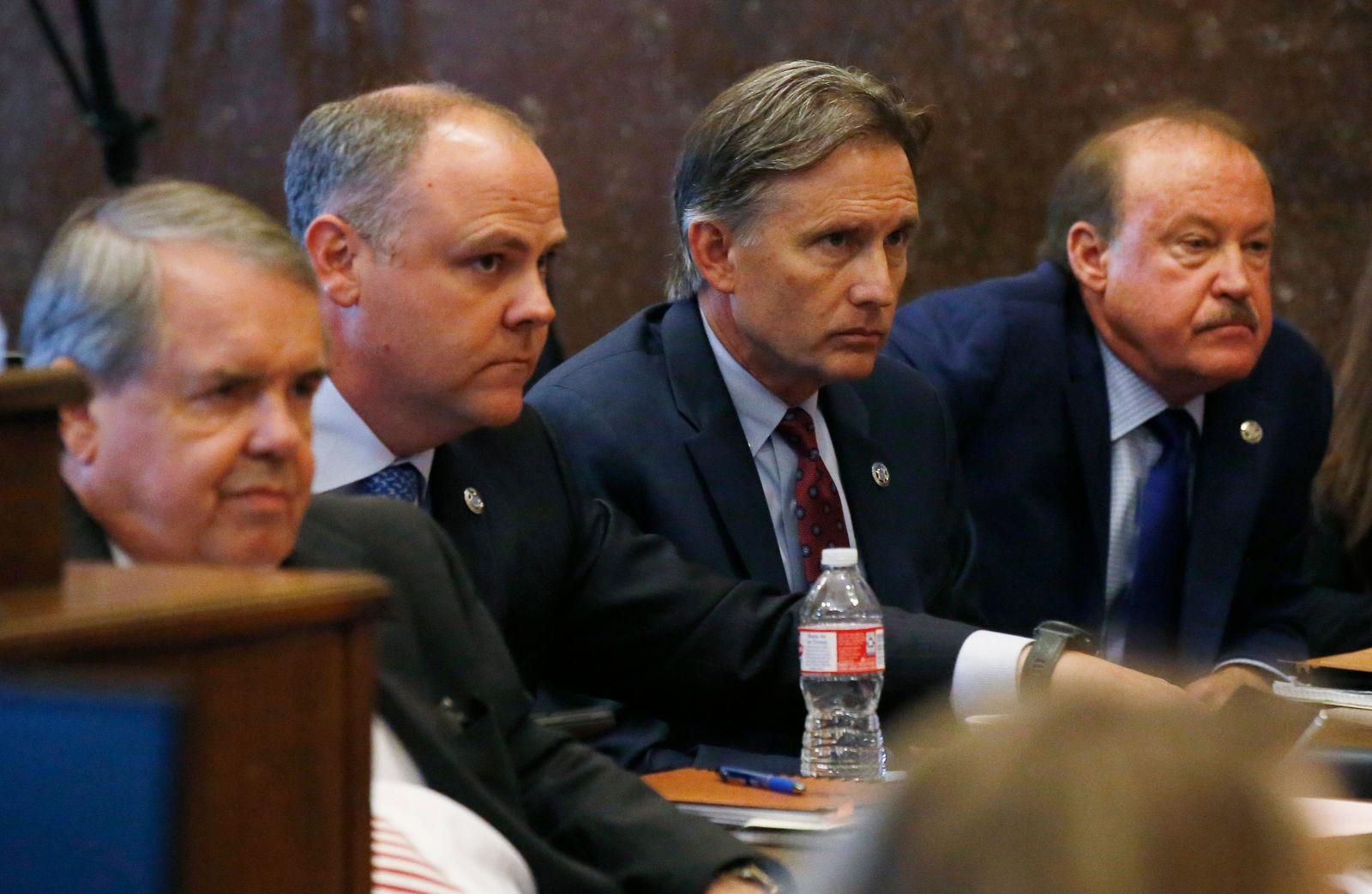 Oklahoma Attorney General Mike Hunter, second from right, listens with members of his team as the judge speaks following closing arguments in Oklahoma's ongoing opioid drug lawsuit against Johnson & Johnson, Monday, July 15, 2019, in Norman, Okla. From left are Michael Burrage, Brad Beckworth, Hunter and Reggie Whitten. (AP Photo/Sue Ogrocki, Pool)