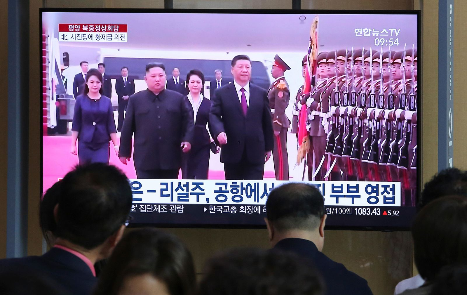 "People watch a TV showing North Korean leader Kim Jong Un, second from left, welcoming Chinese President Xi Jinping at Pyongyang airport, at the Seoul Railway Station in Seoul, South Korea, Friday, June 21, 2019. North Korea's state media says leader Kim Jong Un and Chinese President Xi Jinping held broad discussions over the political situation surrounding the Korean Peninsula and called for stronger bilateral ties in the face of ""serious and complicated changes"" in the region. The signs read: "" Kim Jong Un and his wife Ri Sol Ju welcome Xi Jinping and his wife."" (AP Photo/Ahn Young-joon)"