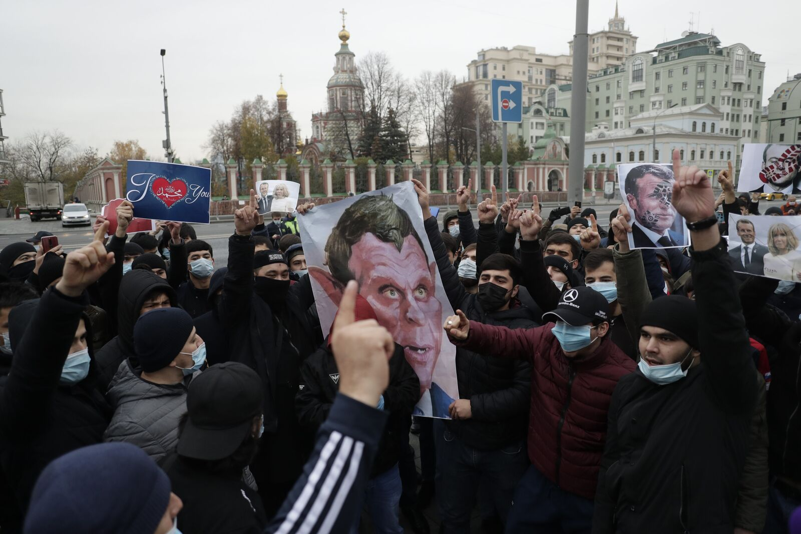 People wearing face masks to help curb the spread of the coronavirus, hold portraits of France President Emmanuel Macron gather outside the French embassy in Moscow to protest against caricatures of the Prophet Muhammad, Russia, Friday, Oct. 30, 2020.(AP Photo/Pavel Golovkin)