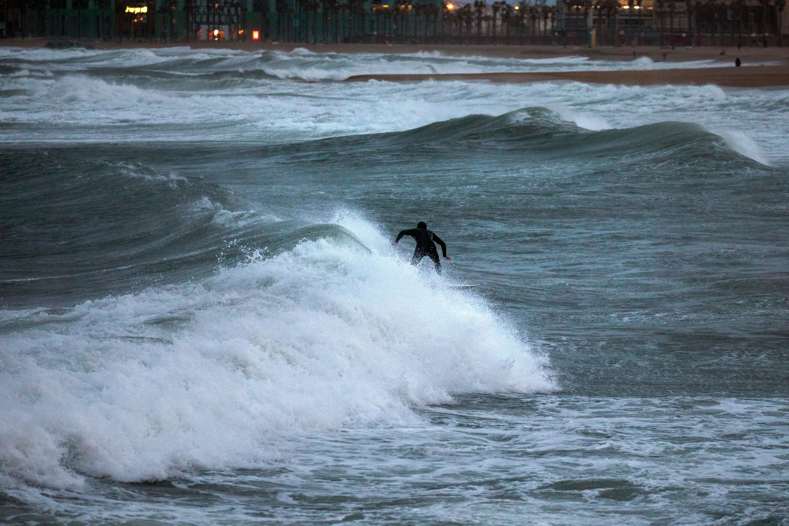 A man surfs the Mediterranean sea during strong winds in Barcelona, Spain, Sunday, Jan. 19, 2020. (AP Photo/Emilio Morenatti)