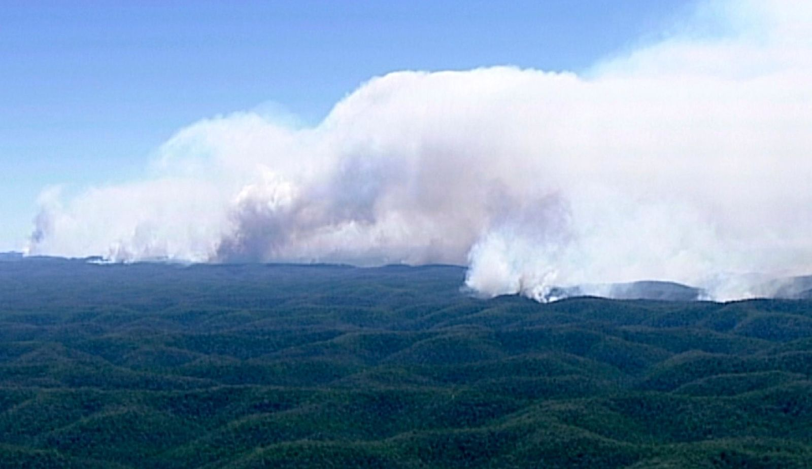 In this image made from video, huge plumes of smoke billow from wildfires in forest in Wollemi, New South Wales state, Australia, Wednesday, Nov. 13, 2019. (Australian Broadcasting Corporation via AP)