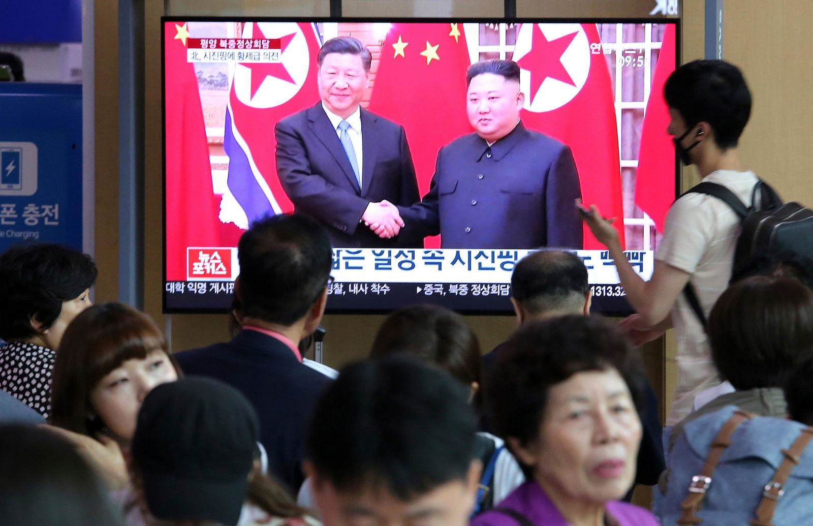 "People watch a TV screen showing North Korean leader Kim Jong Un, right, welcoming Chinese President Xi Jinping, at the Seoul Railway Station in Seoul, South Korea, Friday, June 21, 2019. North Korea's state media says leader Kim Jong Un and Chinese President Xi Jinping held broad discussions over the political situation surrounding the Korean Peninsula and called for stronger bilateral ties in the face of ""serious and complicated changes"" in the region. The signs read: ""Xi Jinping has a lot of schedules."" (AP Photo/Ahn Young-joon)"