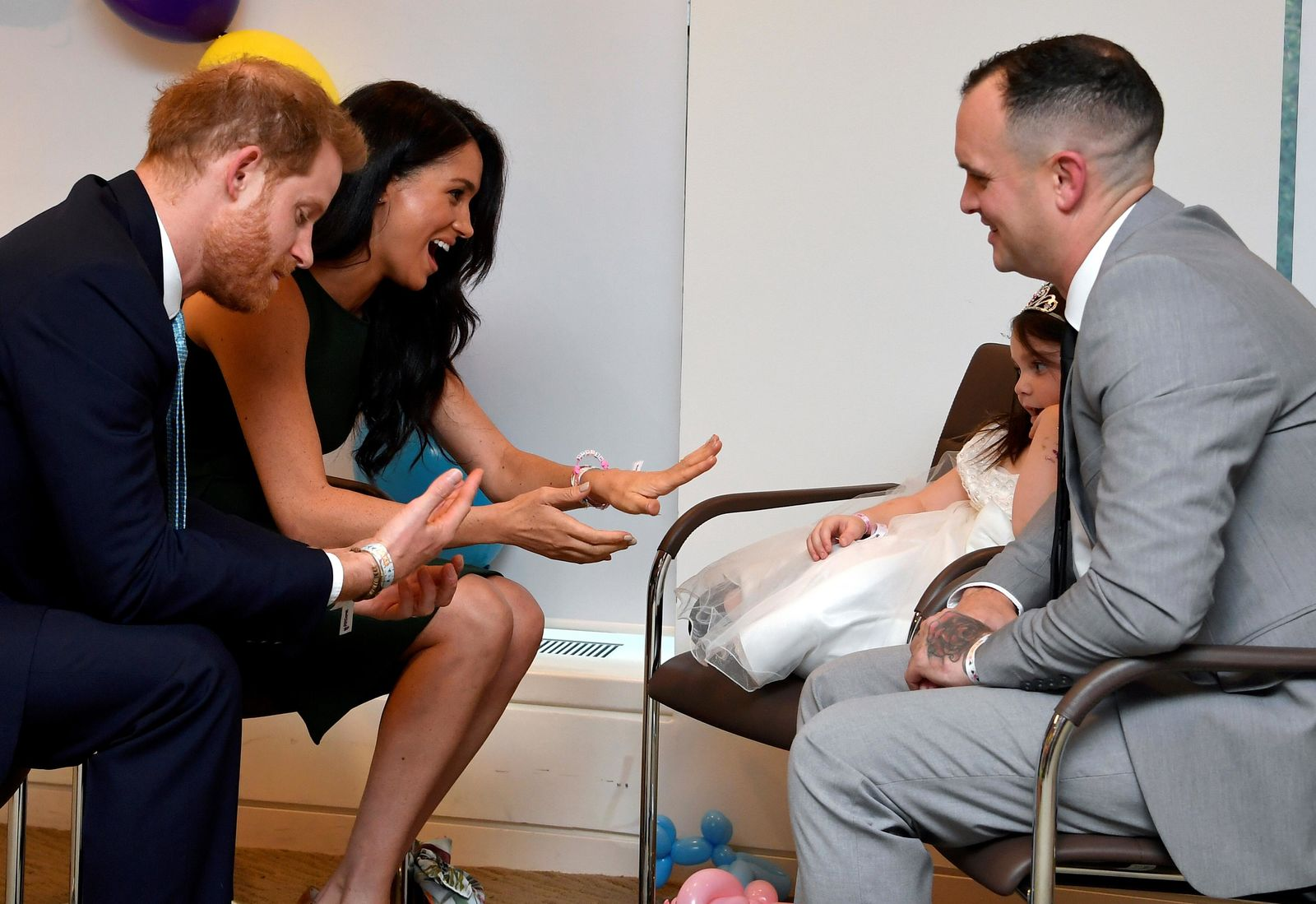 Britain's Prince Harry and Duchess of Sussex, left, react as they are given bracelets by Lyla-Rose O'Donovan and her father Paul, during the annual WellChild Awards in London, Tuesday Oct. 15, 2019. The WellChild Awards celebrate the inspiring qualities of some of the country's seriously ill young people.(Toby Melville/Pool via AP)