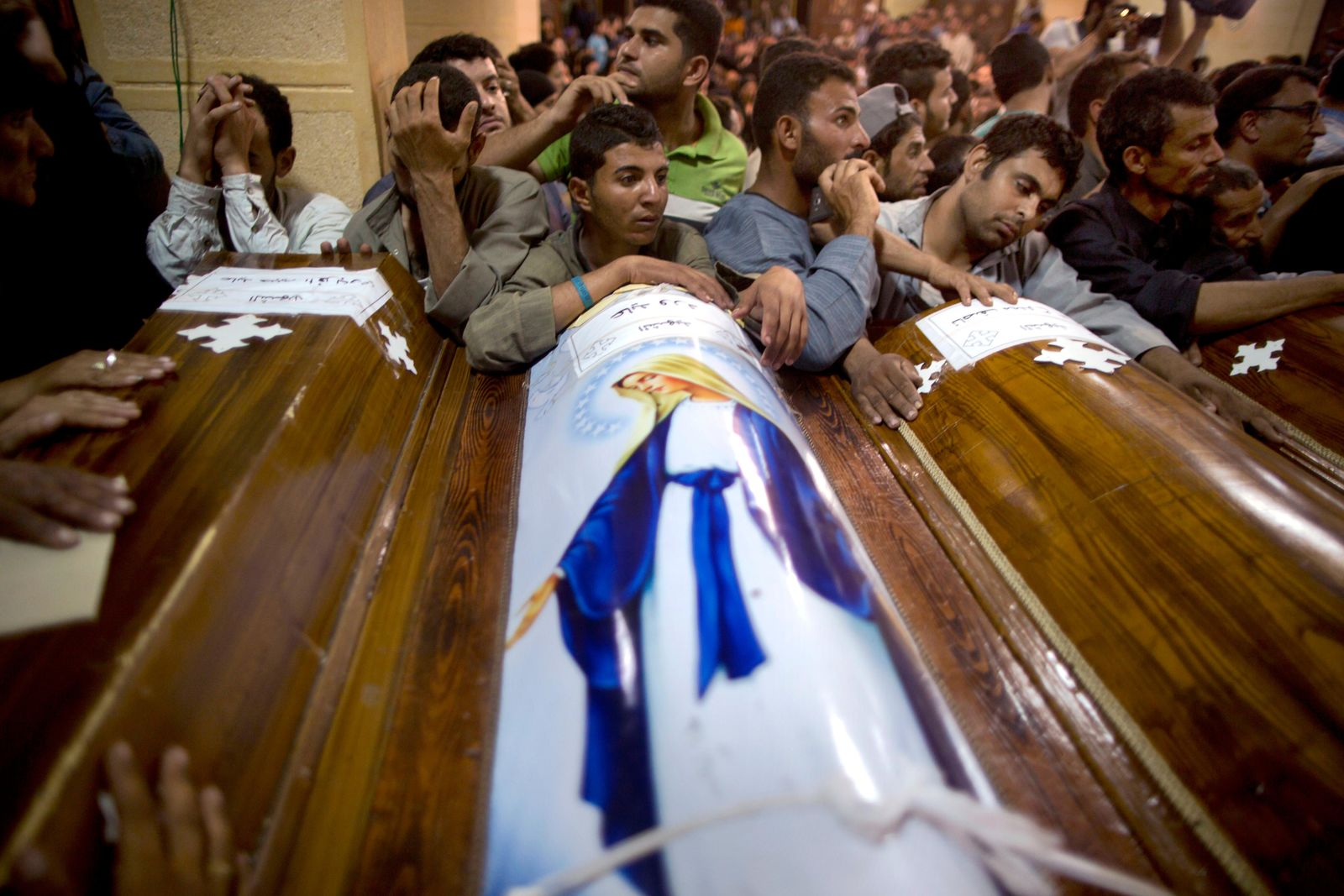 Relatives of Coptic Christians who were killed during a bus attack, surround their coffins, during their funeral service, at Abu Garnous Cathedral in Minya, Egypt, Friday, May 26, 2017. (AP Photo/Amr Nabil)