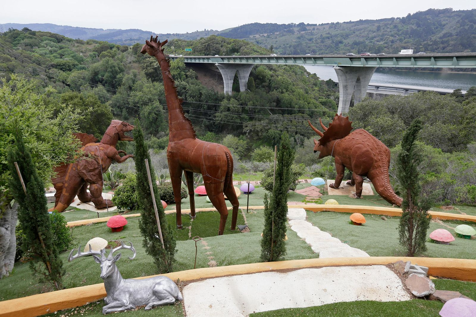 In this photo taken Monday, April 1, 2019, dinosaurs and other figures stand outside the Flintstone House overlooking Interstate 280 in Hillsborough, Calif. The San Francisco Bay Area suburb of Hillsborough is suing the owner of the house, saying that she installed dangerous steps, dinosaurs and other Flintstone-era figurines without necessary permits.  (AP Photo/Eric Risberg)