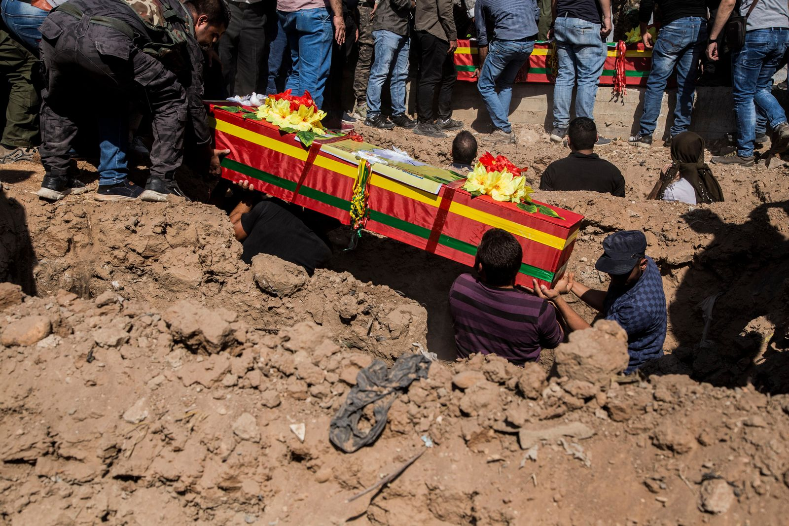 People attend funerals of fighters of the Syrian Democratic Forces killed fighting Turkish advance, in the town of Qamishli, northern Syria, Wednesday, Oct. 16, 2019. (AP Photo/Baderkhan Ahmad)