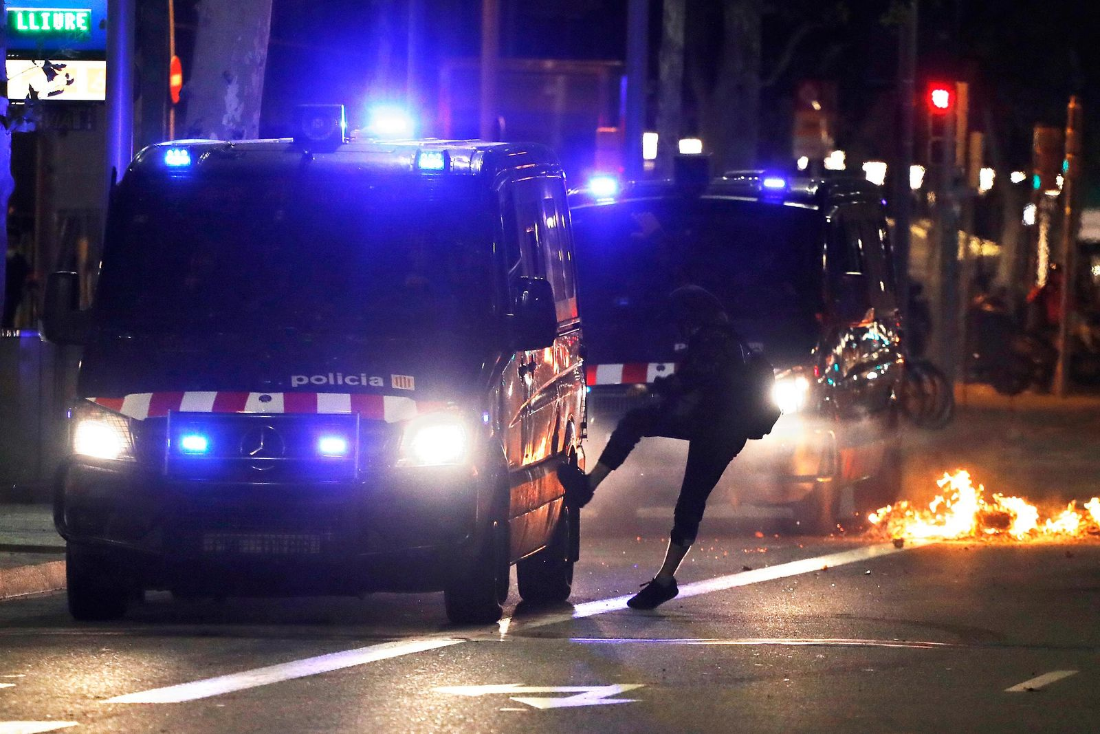 A protestor kicks a police van during clashes in Barcelona, Spain, Thursday, Oct. 17, 2019.{ } (AP Photo/Emilio Morenatti)