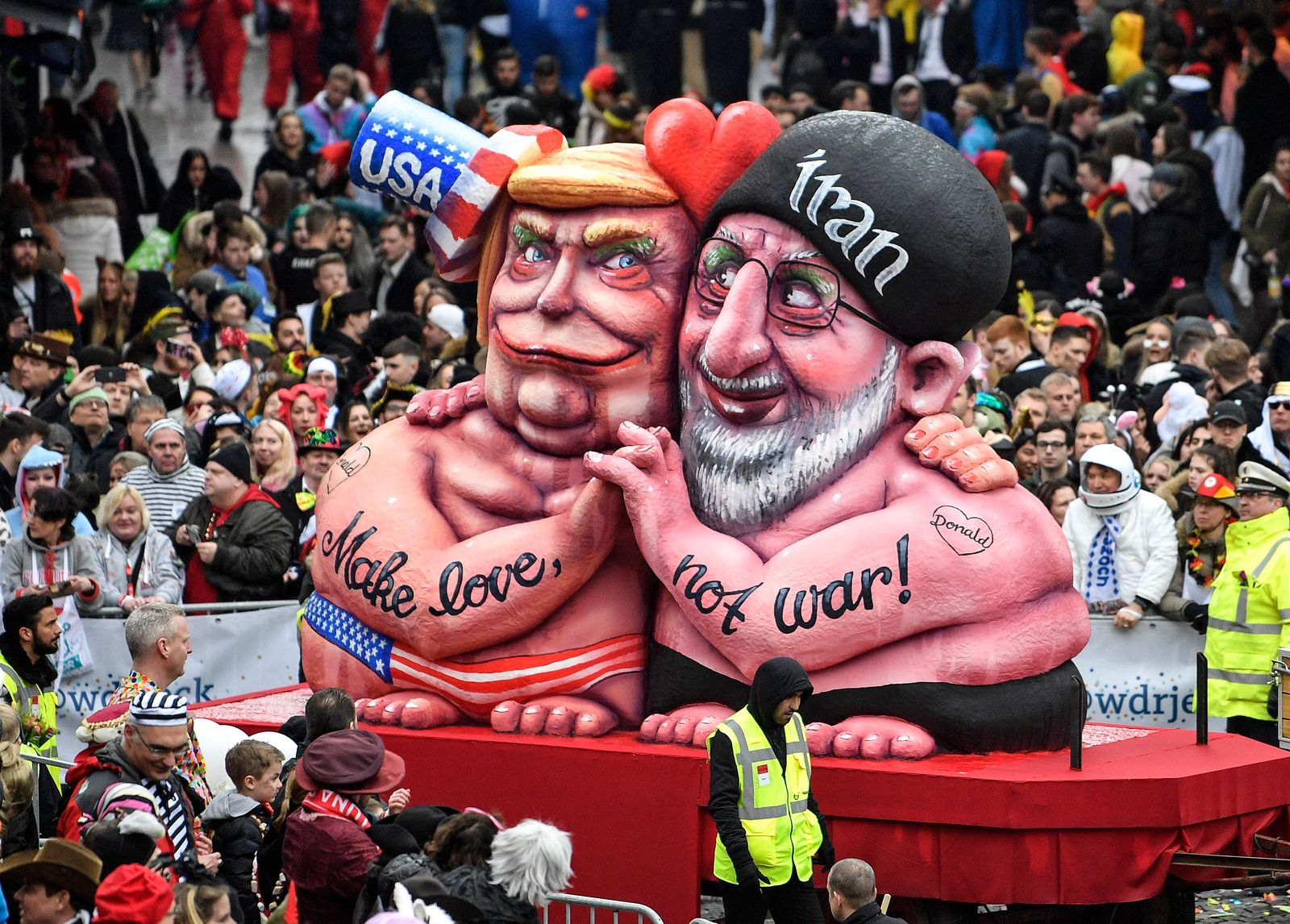 A carnival float depicts US President Donald Trump holding hands with Iran's President Hassan Rohani during the traditional carnival parade in Duesseldorf, Germany, on Monday, Feb. 24, 2020. The foolish street spectacles in the carnival centers of Duesseldorf, Mainz and Cologne, watched by hundreds of thousands of people, are the highlights in Germany's carnival season on Rosemonday. (AP Photo/Martin Meissner)