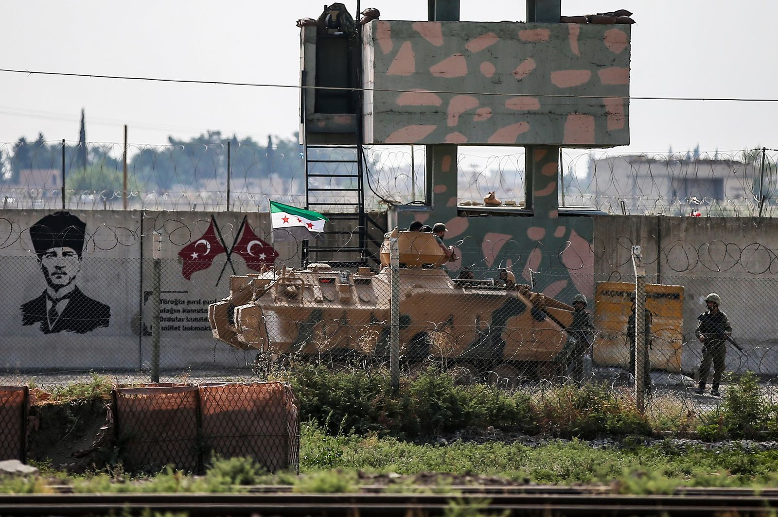 Turkish-backed Syrian opposition fighters on an armoured personnel carrier drive to cross the border into Syria, in Akcakale, Sanliurfa province, southeastern Turkey, Friday, Oct. 18, 2019. (AP Photo/Emrah Gurel)