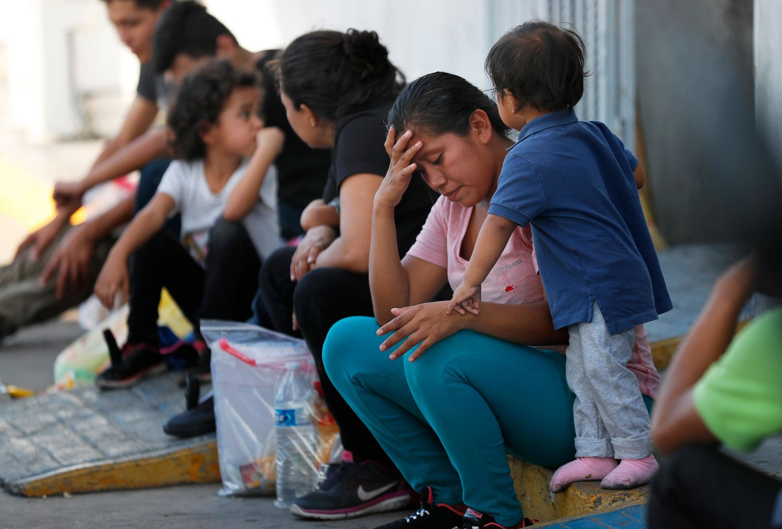 Migrants wait at an immigration center on the International Bridge 1, in Nuevo Laredo, Mexico, Tuesday, July 16, 2019. (AP Photo/Marco Ugarte)