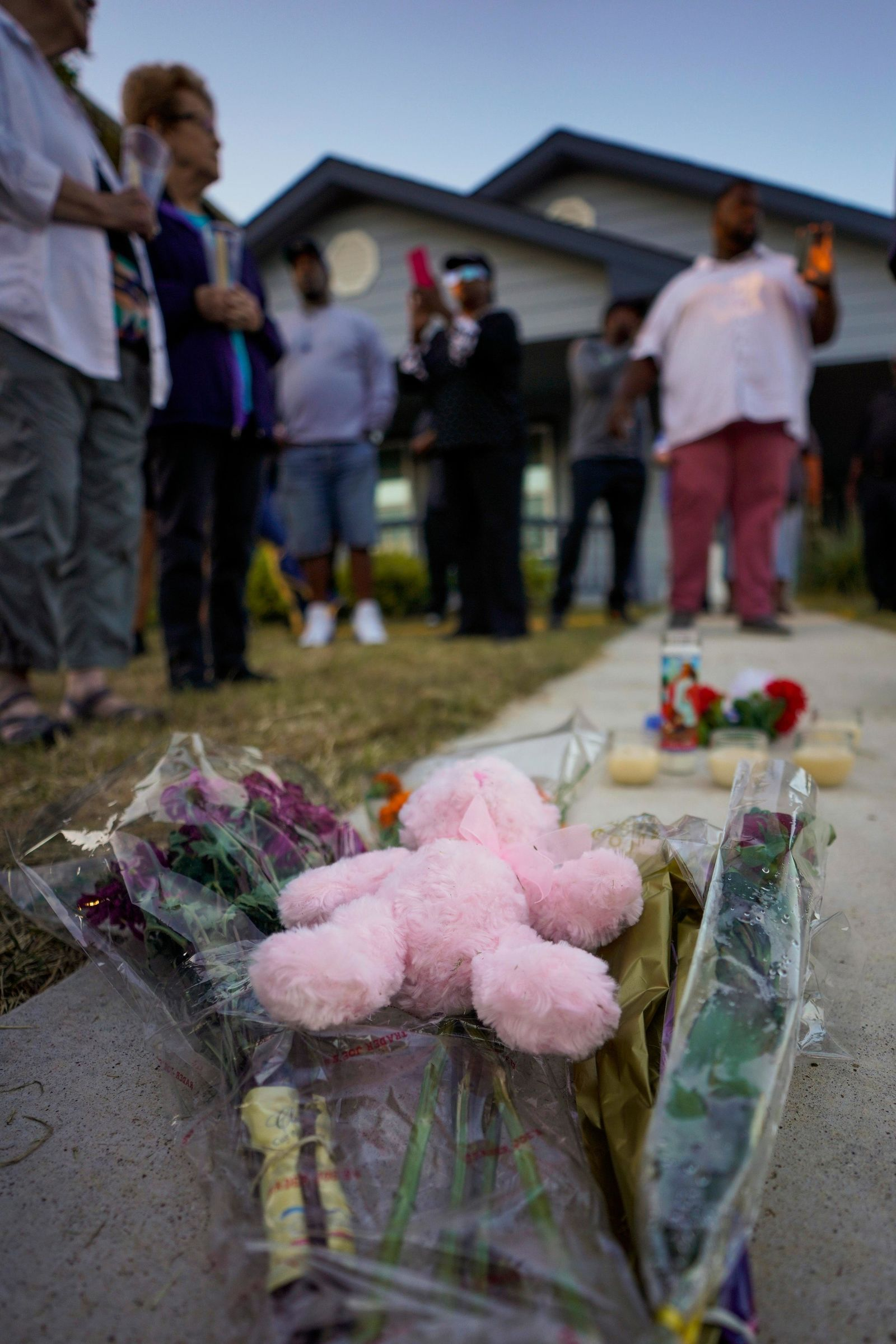"Protesters left flowers outside the house, in the background, where Atatiana Jefferson was shot and killed, durin a community vigil for Atatiana Jefferson on Sunday, Oct. 13, 2019, in Fort Worth, Texas. A white police officer who killed the black woman inside her Texas home while responding to a neighbor's call about an open front door ""didn't have time to perceive a threat"" before he opened fire, an attorney for Jefferson's family said. (Smiley N. Pool/The Dallas Morning News via AP)"