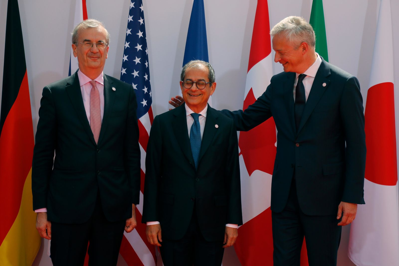 French Finance Minister Bruno Le Maire, right, welcomes Italian Economy and Finance Minister Giovanni Tria , center, with Governor of the Bank of France Francois Villeroy de Galhau, at the G-7 Finance Wednesday July 17, 2019. (AP Photo/Michel Euler)