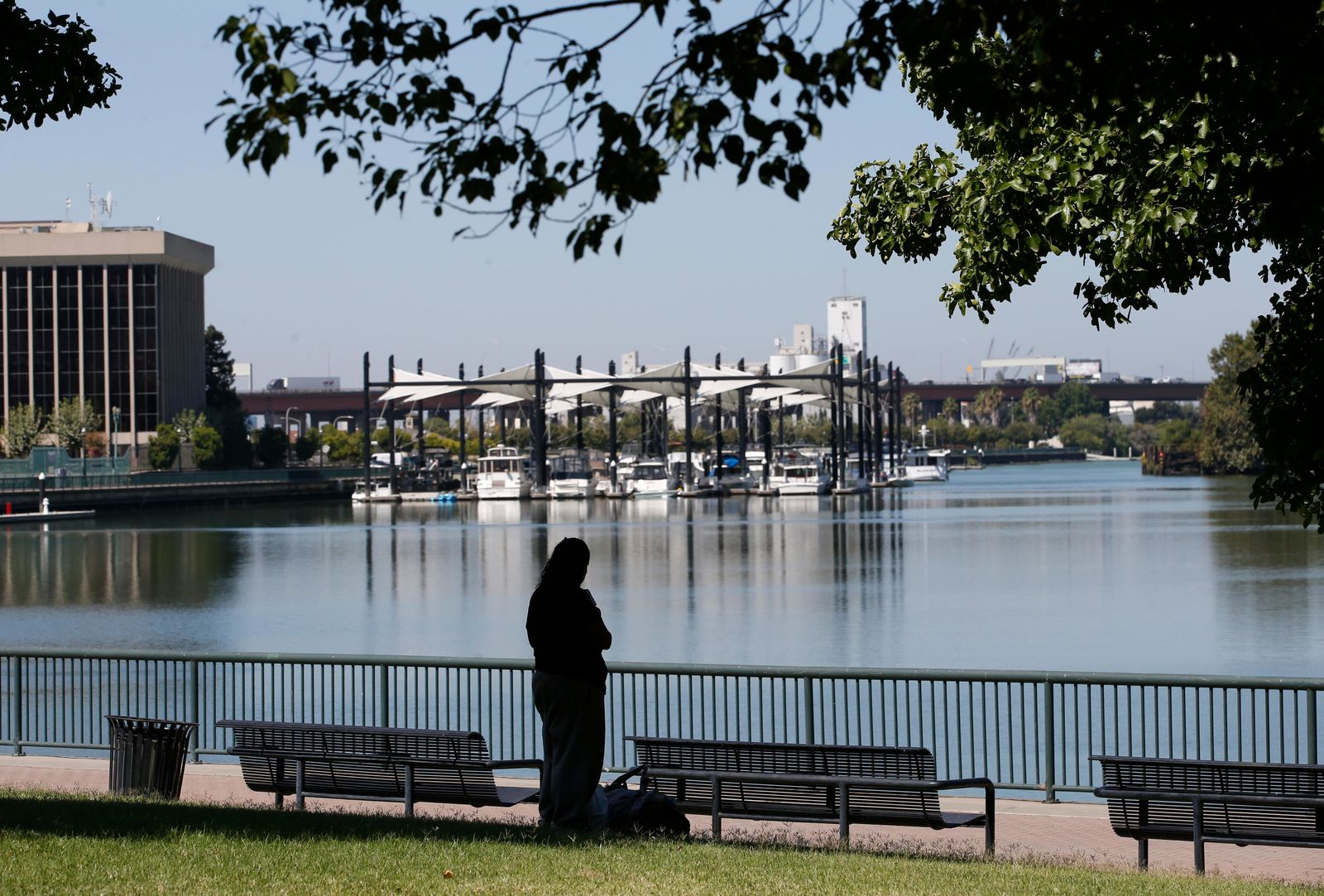 In this photo taken Wednesday, Aug. 14, 2019, a visitor takes in the view of the waterfront in Stockton, Calif. The area as been targeted for redevelopment as Stockton continues to revere from the Great Recession when it known as the foreclosure capital of the country and for one of the nation's largest municipal bankruptcies. Now, it's led by Mayor Michael Tubbs who has initiated a program to give 125 people who earn at or below the median household income of $46,033 receive a $500 debit card each month to spend any what they want. Tubbs says the program, which is privately funded, could be a solution to the city's poverty problem. (AP Photo/Rich Pedroncelli)