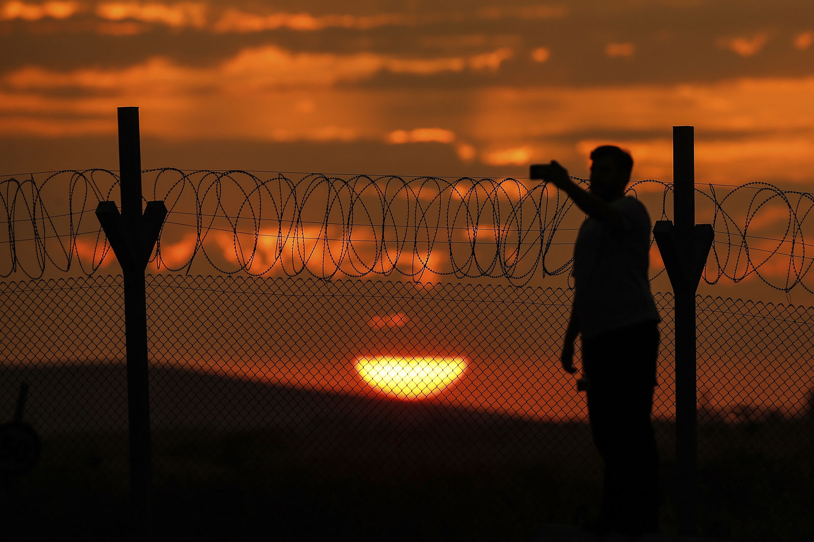 As the sun sets, a journalist uses this mobile to take video at the Karkamis border gate with Syria at Gaziantep province, southeastern Turkey, Wednesday, Oct. 16, 2019.  Turkey's President Recep Tayyip Erdogan called Wednesday on Syrian Kurdish fighters to leave a designated border area in northeast Syria 'as of tonight' for Turkey to stop its military offensive. (AP Photo/Emrah Gurel)