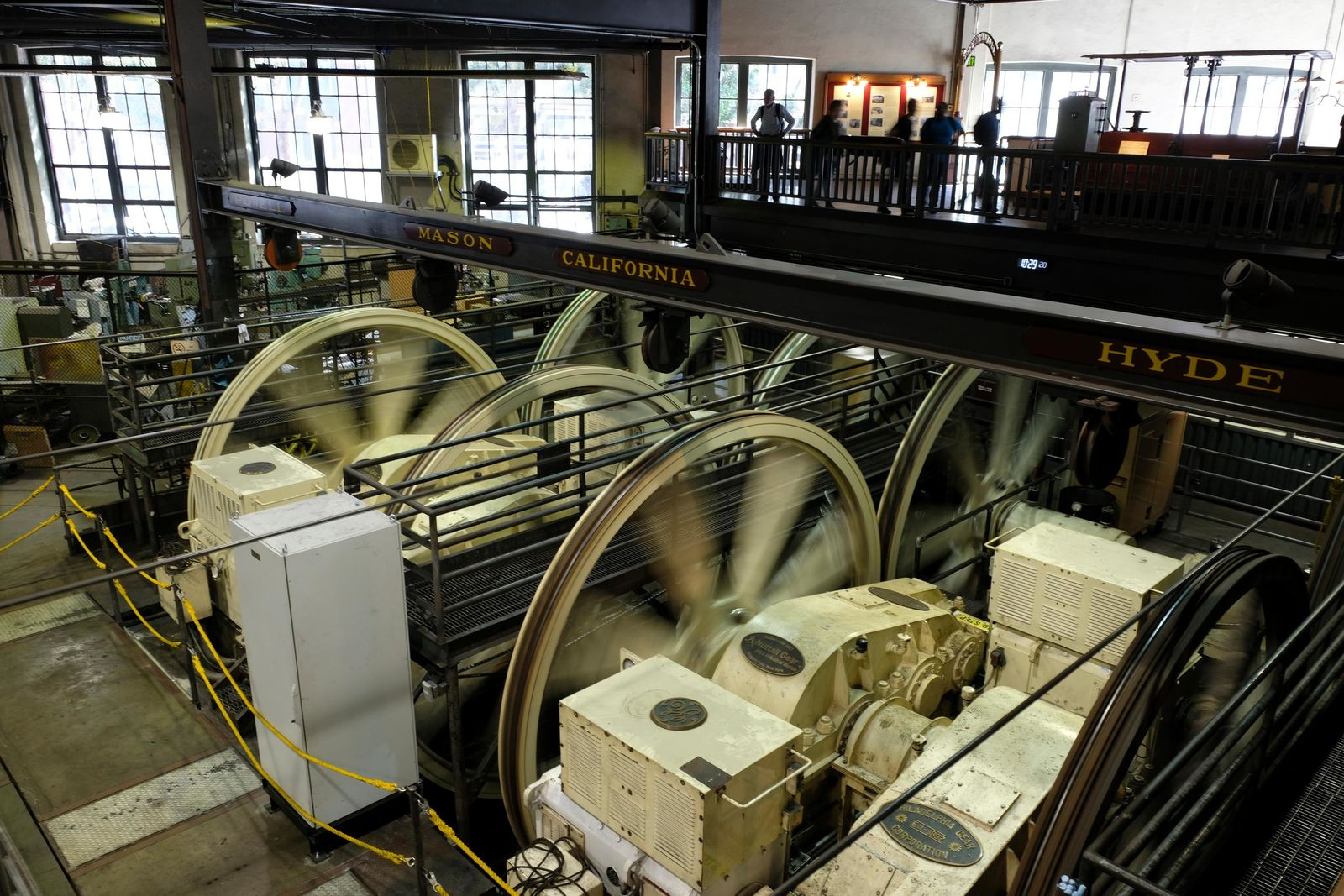 People stand above turning sheaves and gearboxes inside the cable car powerhouse Wednesday, Sept. 11, 2019, in San Francisco. (AP Photo/Eric Risberg)