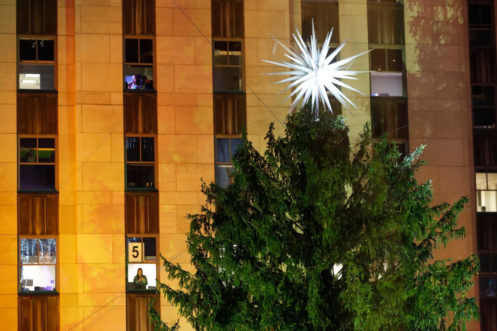 A woman waits in a fifth floor window for the 87th annual Rockefeller Center Christmas Tree lighting to begin as entertainment acts continued, Wednesday, Dec. 4, 2019, in New York. (AP Photo/Kathy Willens)